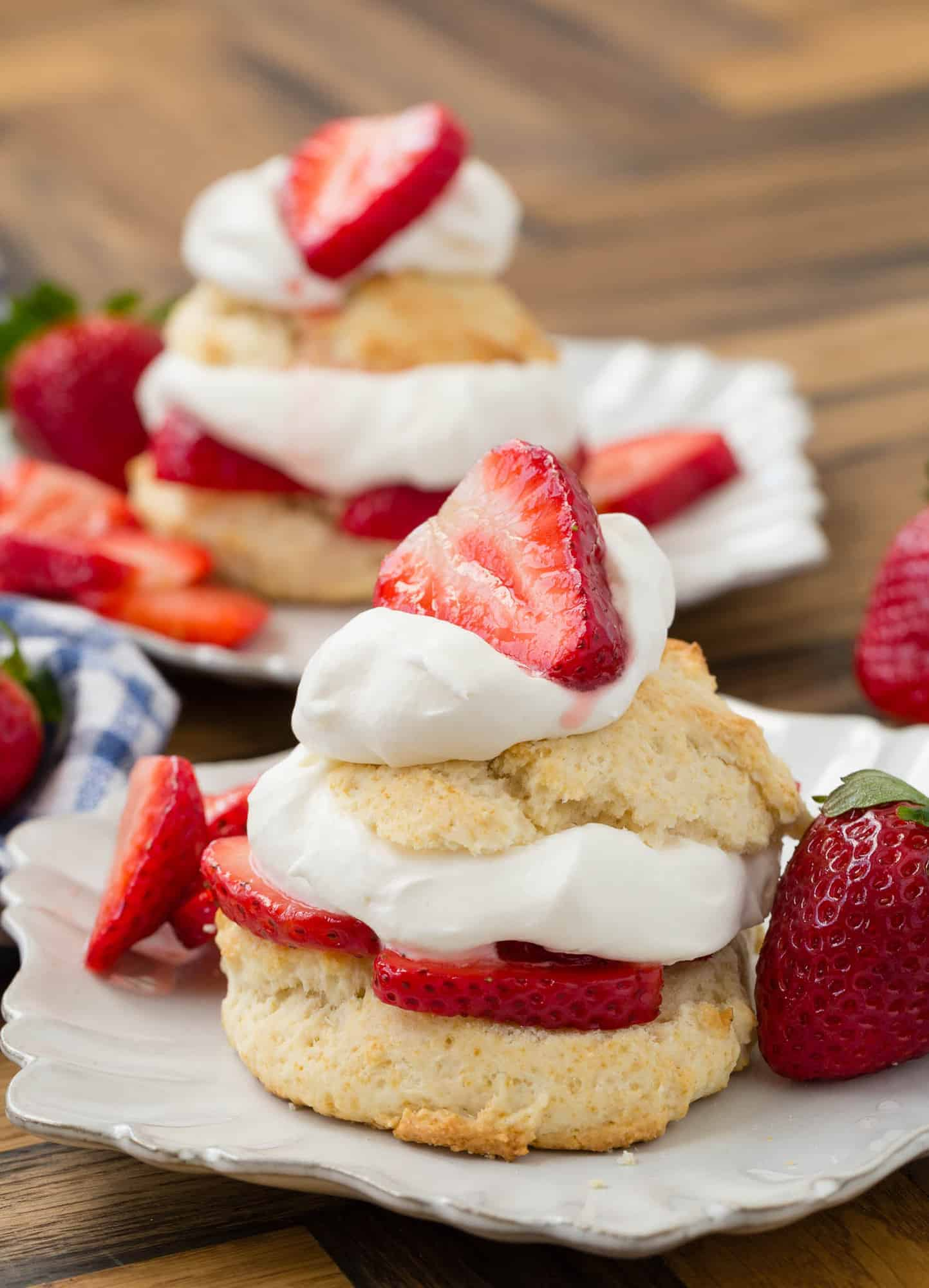 Decorative white plate with strawberry shortcake on it, topped with whipped cream and strawberries.