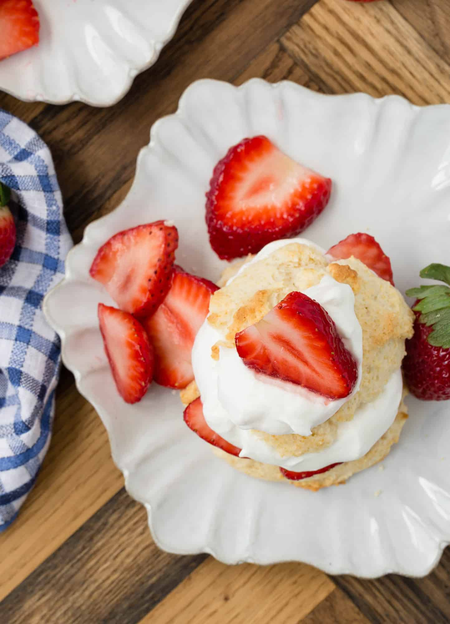 Overhead view of strawberry shortcake on a white plate.