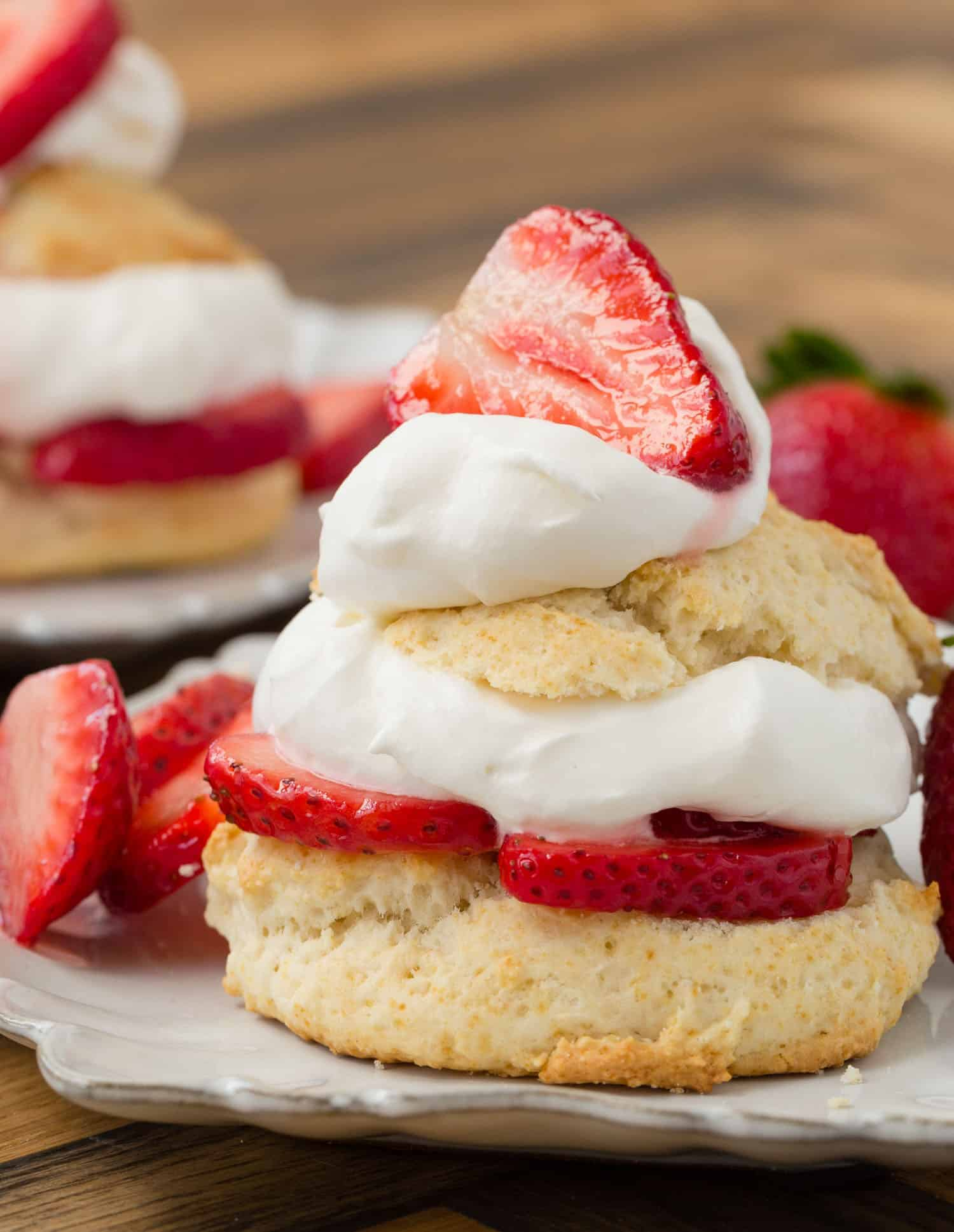 Close up view of strawberry shortcake on a white plate.