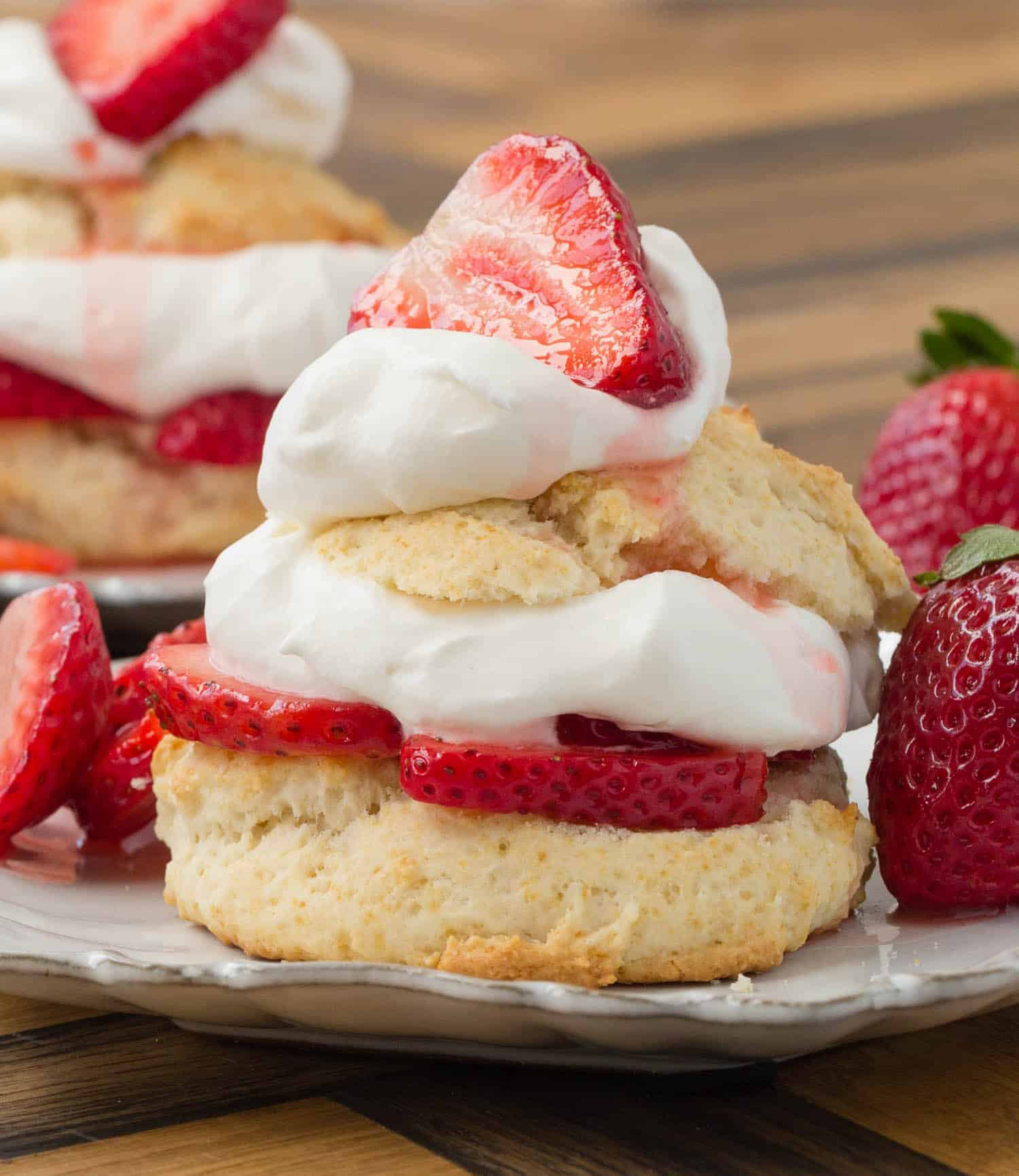 Straight-on view of a shortcake split in half and filled with whipped cream and sliced strawberries.