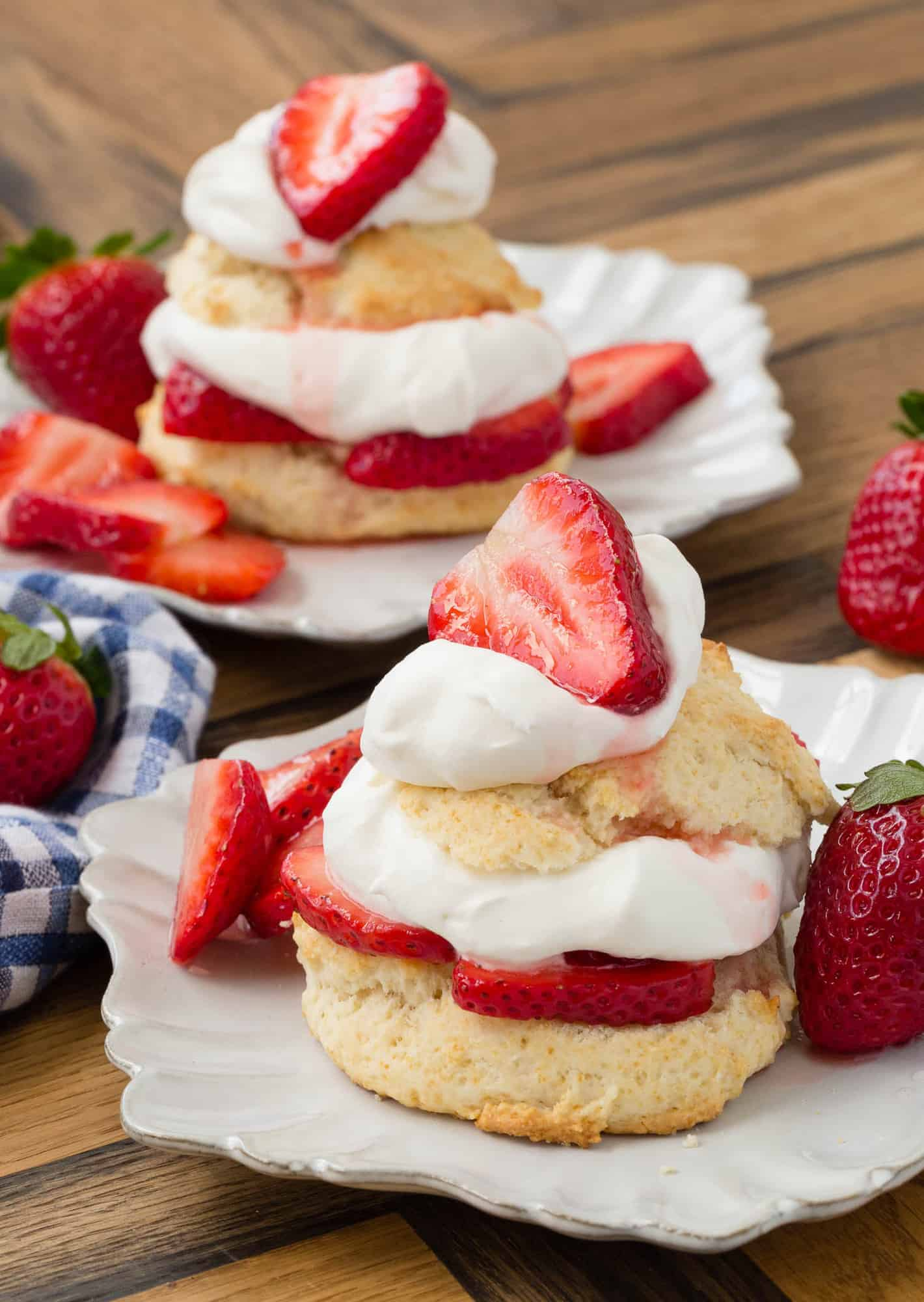 Two white plates with strawberry shortcakes with whipped cream.
