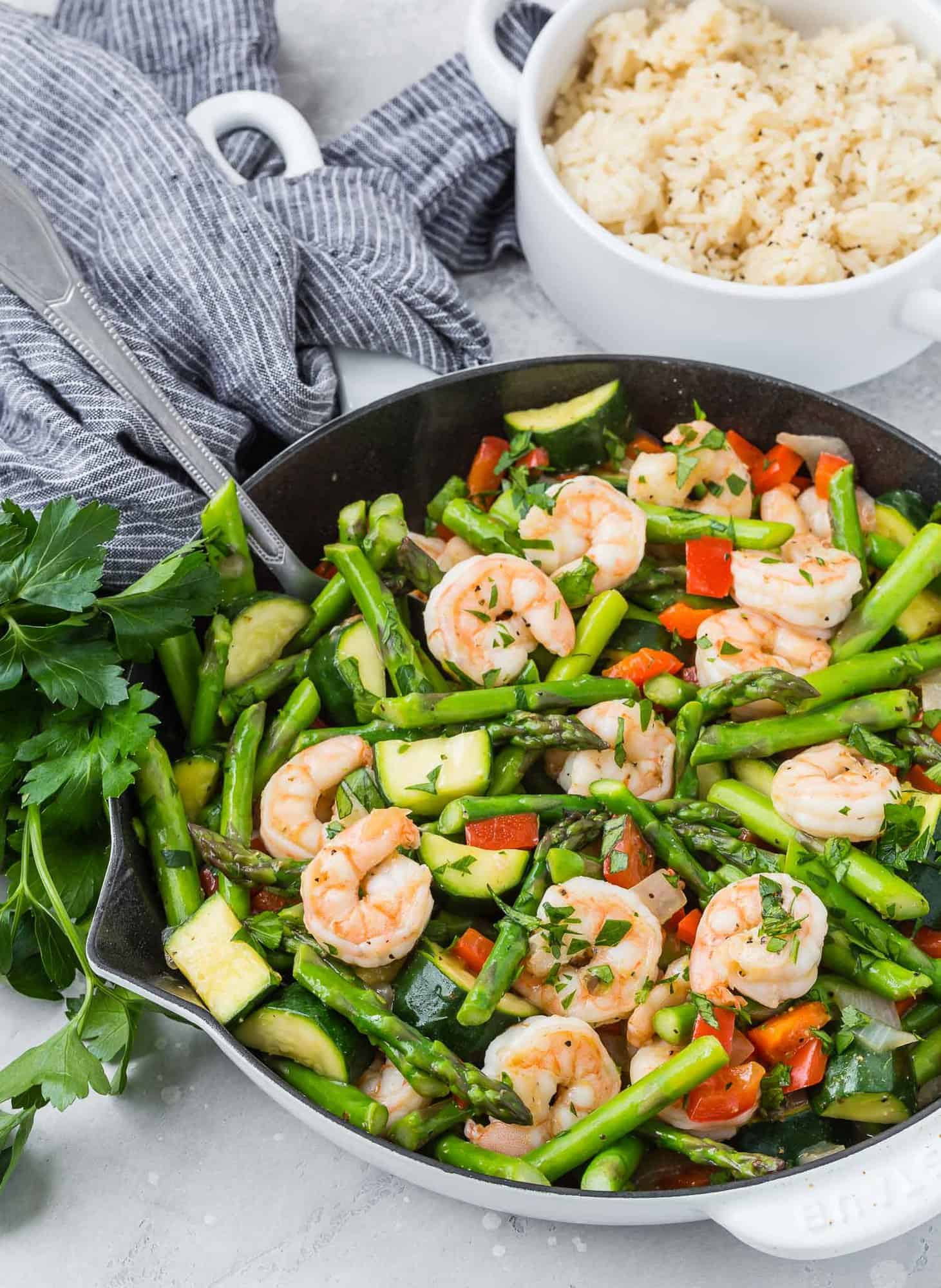 Shrimp stir fry in a white skillet, cooked rice in the background.