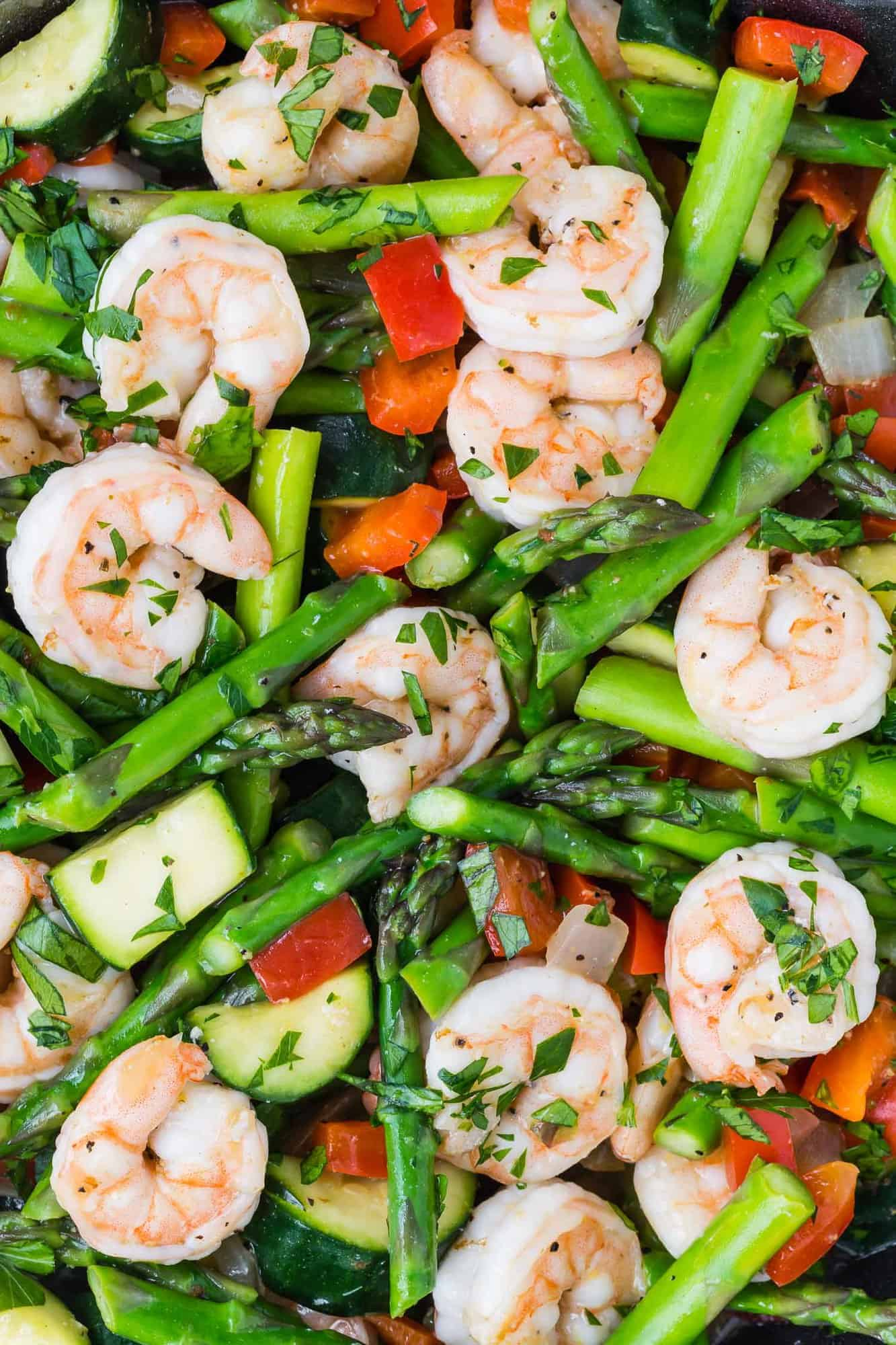 Close up view of a shrimp stir fry with asparagus, zucchini, and red bell peppers.