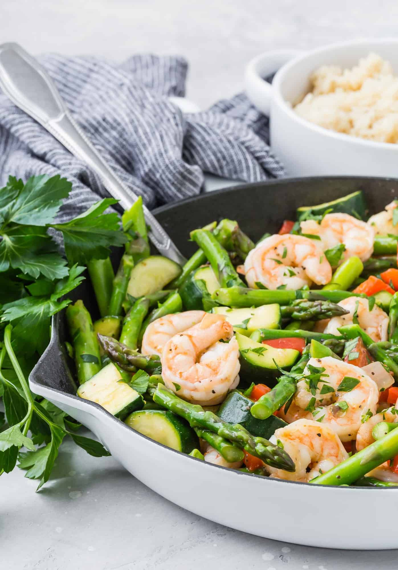 Stir fry with shrimp and asparagus in a white skillet with a silver spoon.