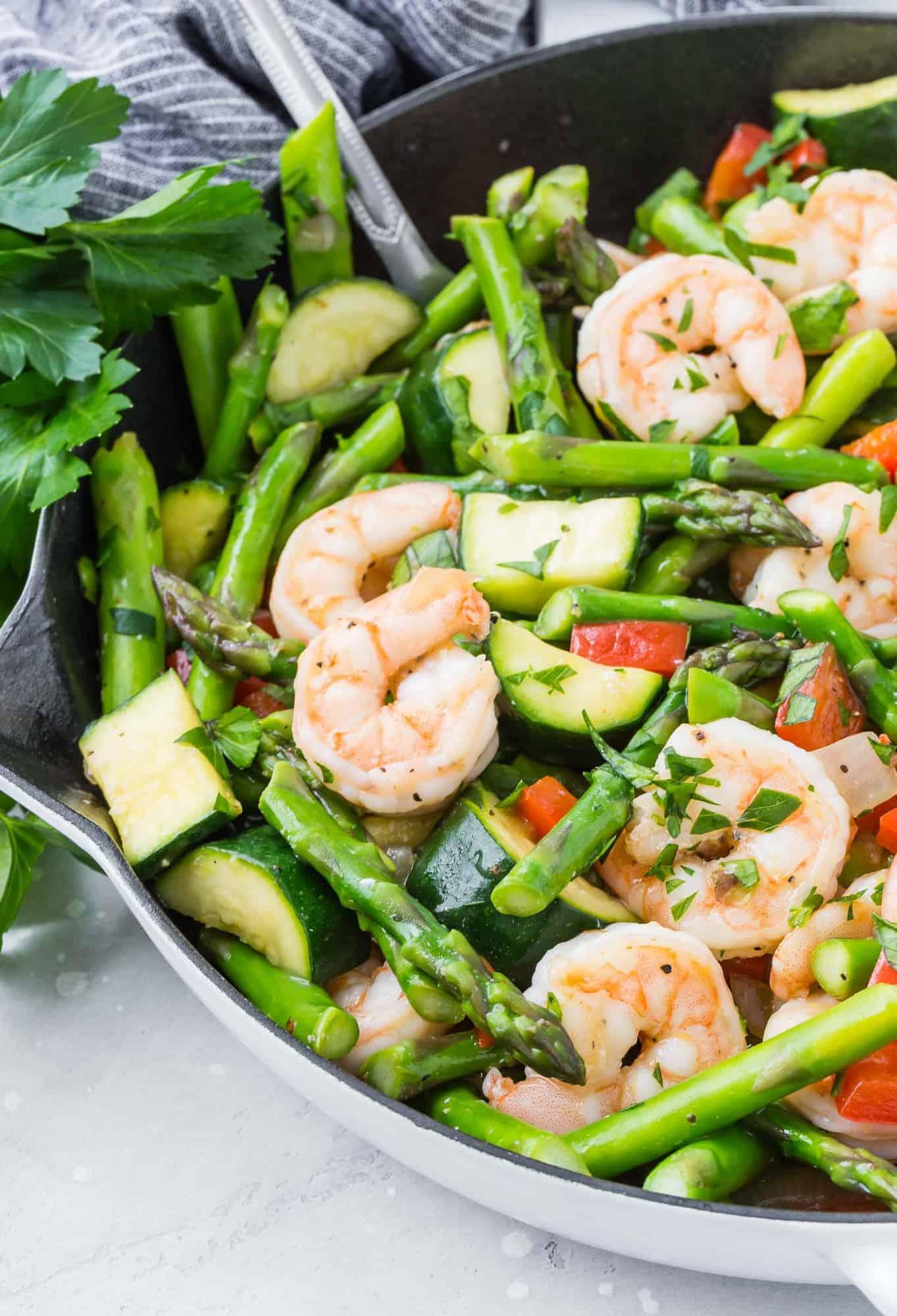 Shrimp and vegetables in a white skillet.