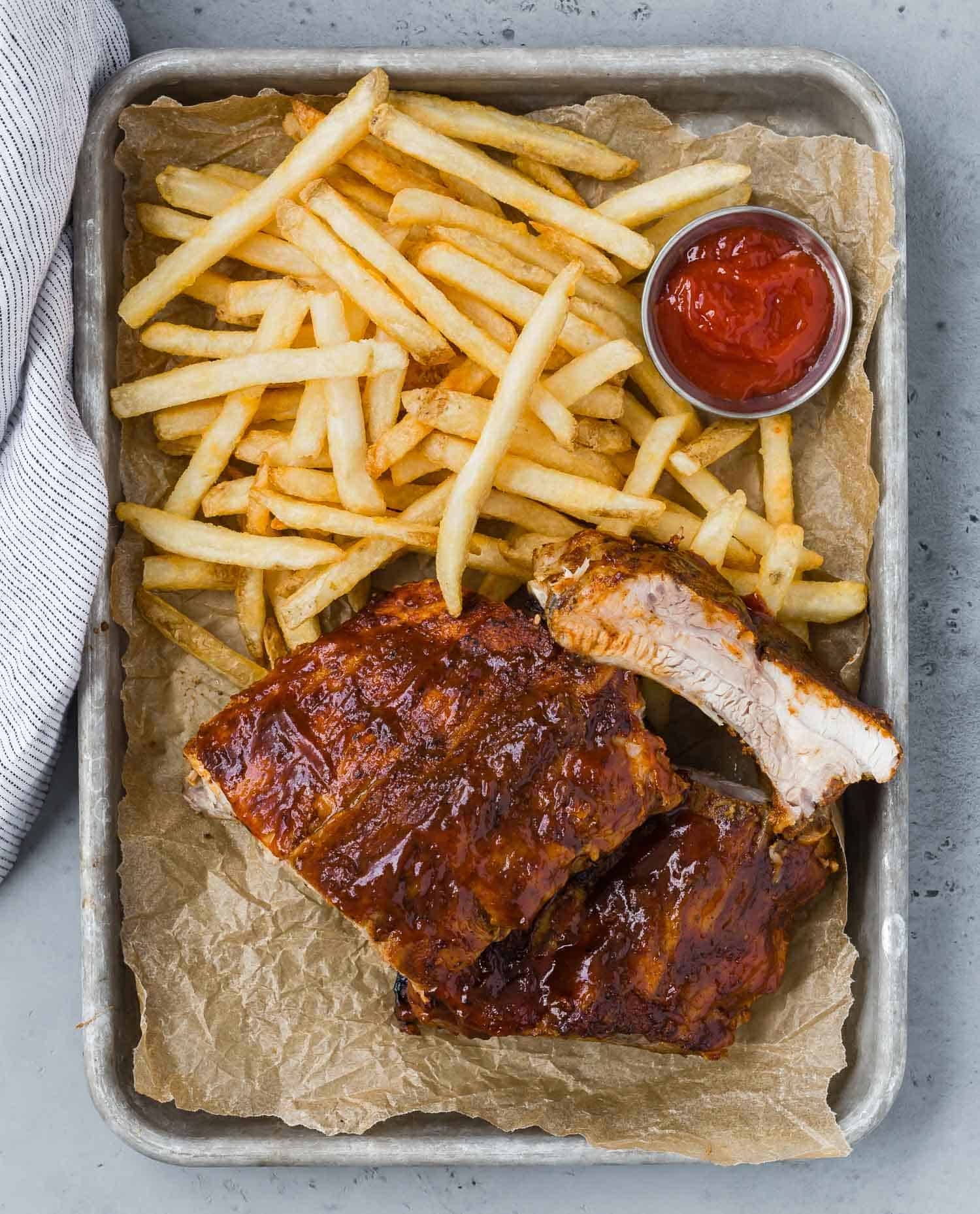 Overhead view of ribs on a tray with fries and ketchup.