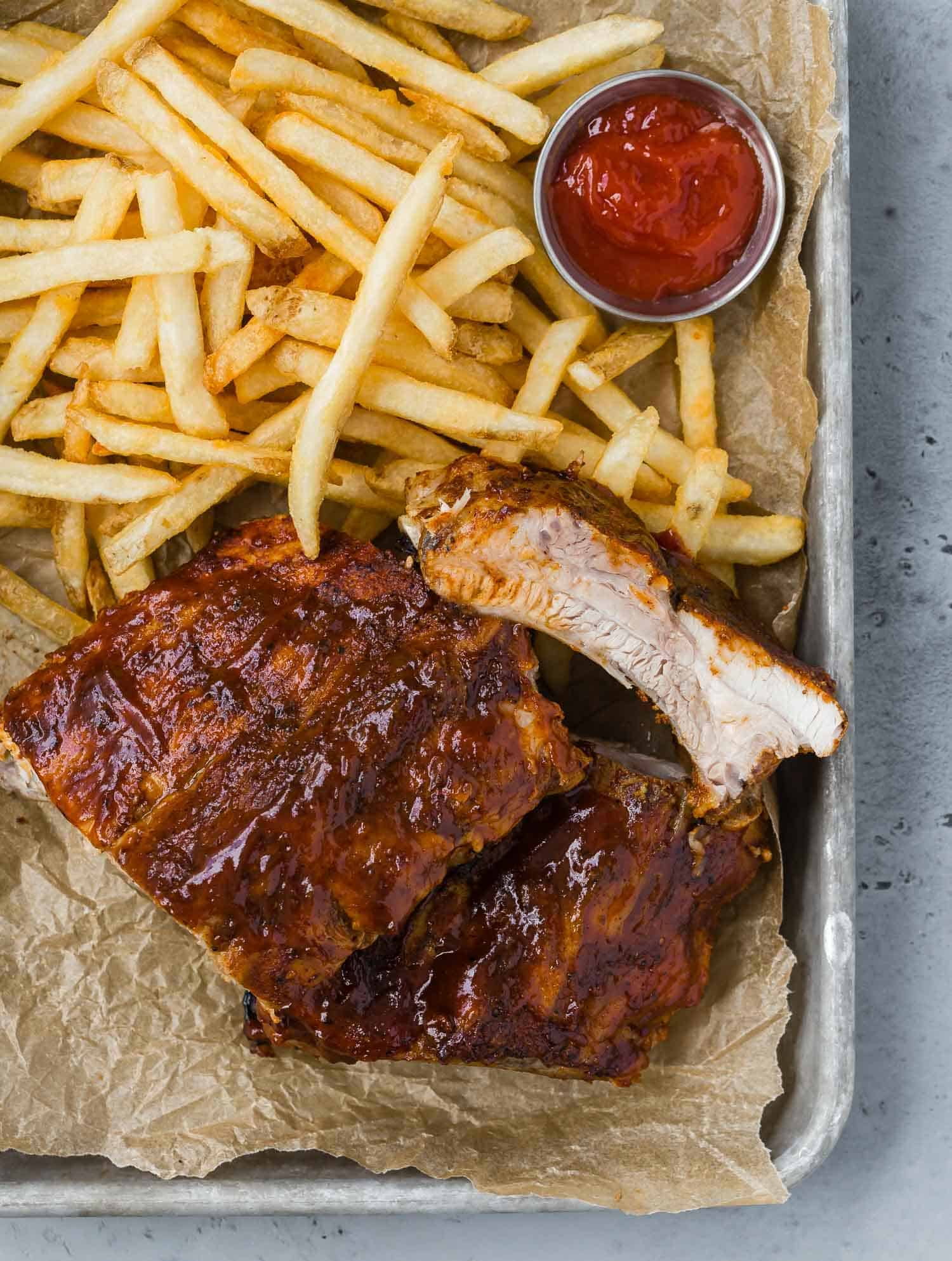 Ribs on a parchment paper lined tray with fries and a small metal cup of ketchup.