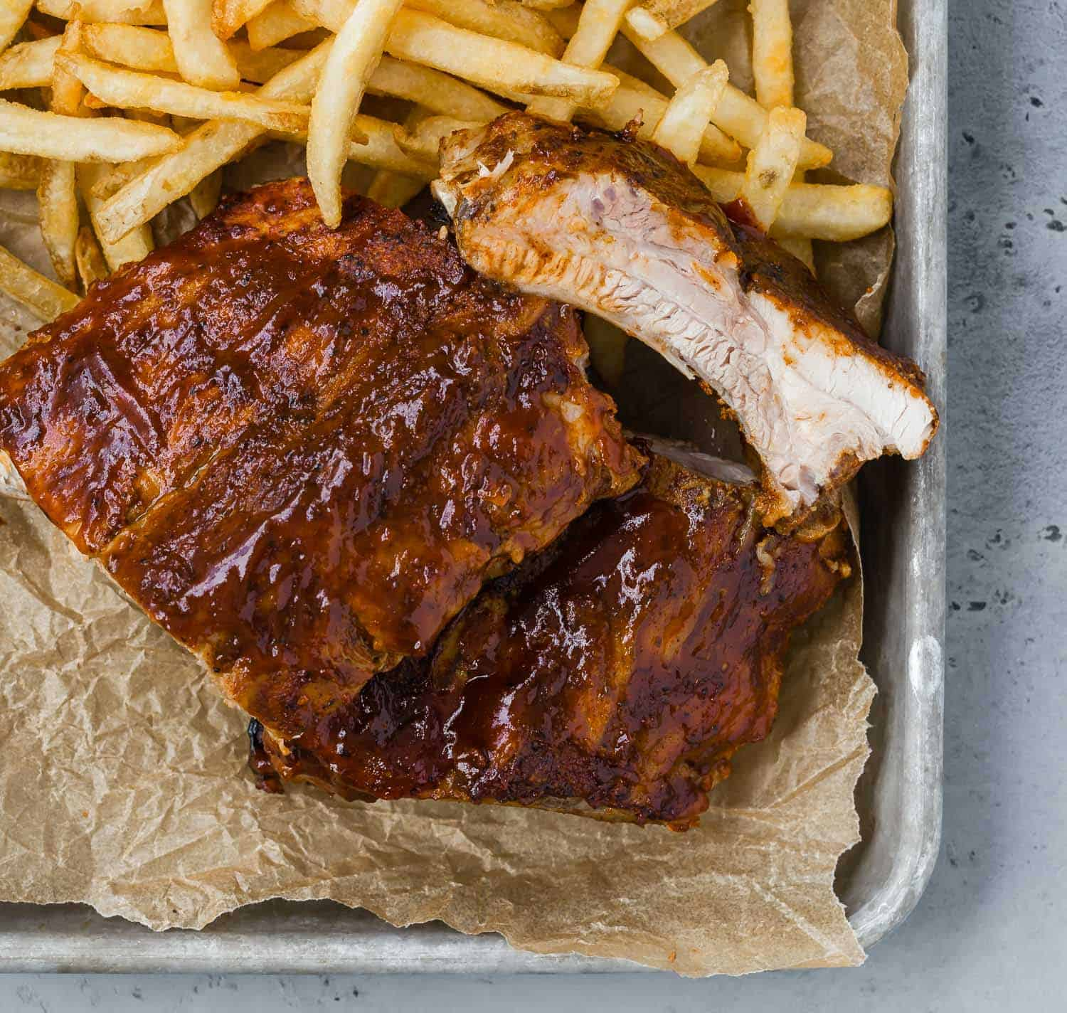 A tray lined with brown parchment, topped with bbq ribs and french fries.