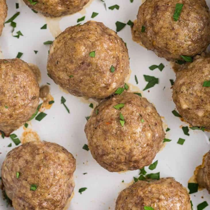 Overhead view of baked meatballs without sauce, sprinkled with parsley.