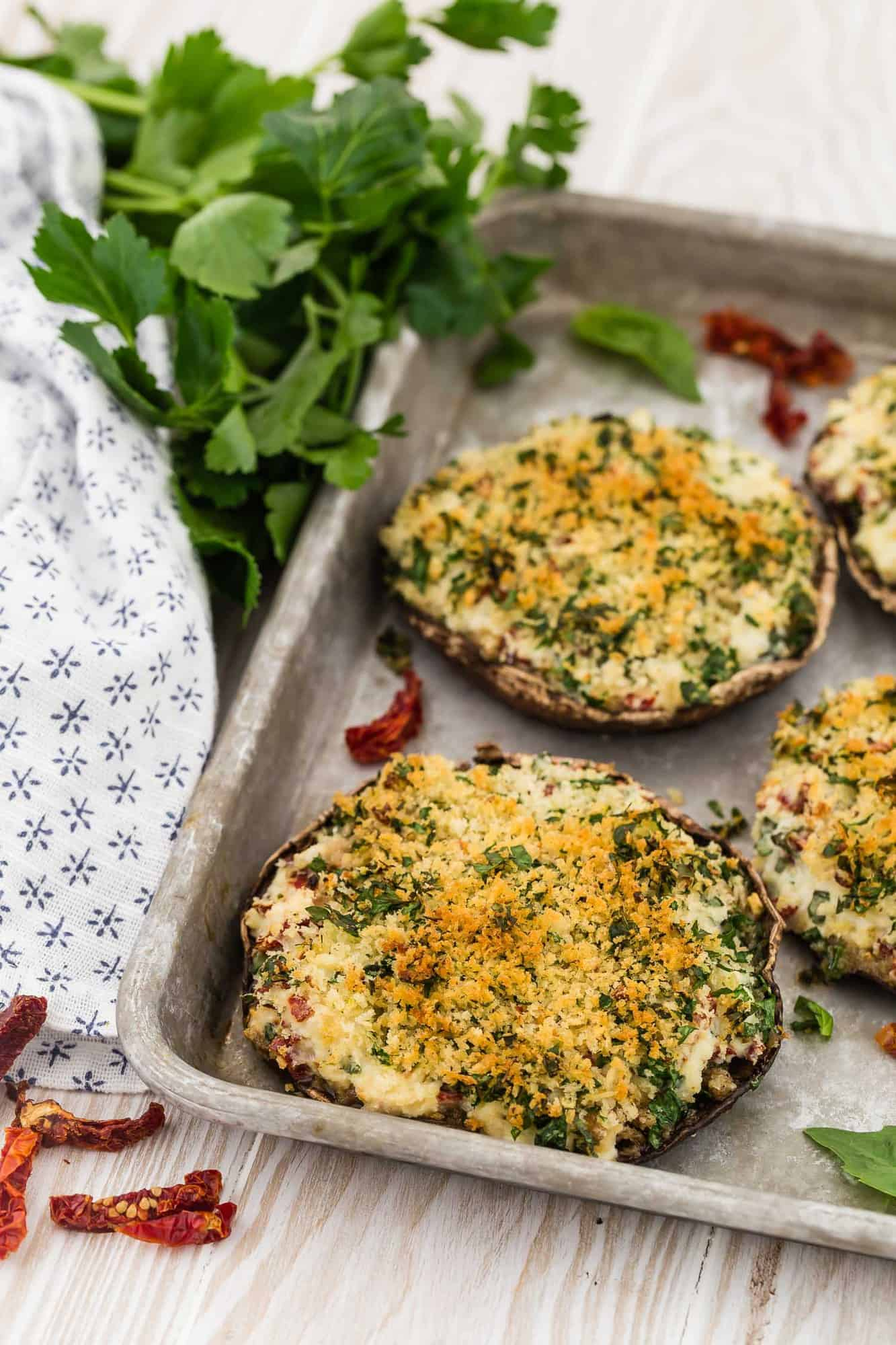 Stuffed mushrooms on a metal baking sheet, with parsley in background.