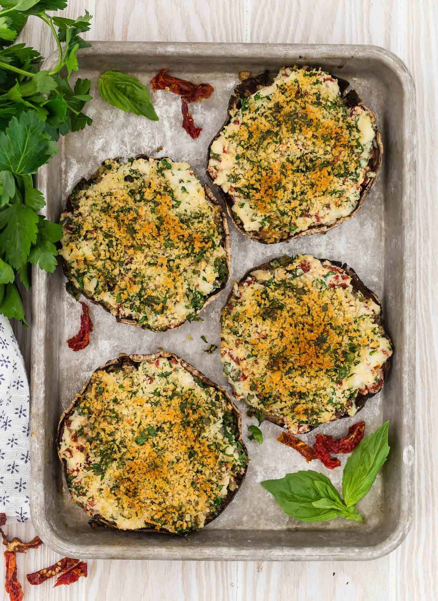 Overhead view of 4 portobello mushrooms on a baking sheet, filled with stuffing and baked.