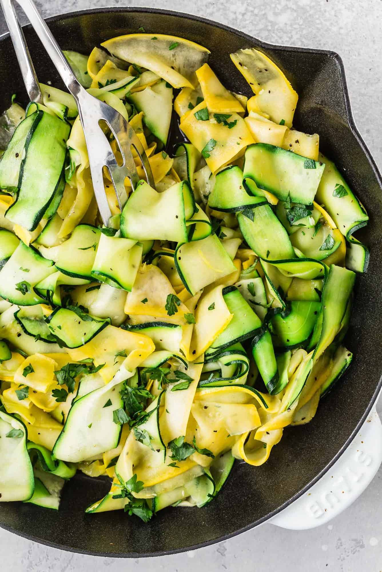 Zucchini and summer squash ribbons in a white and black skillet.