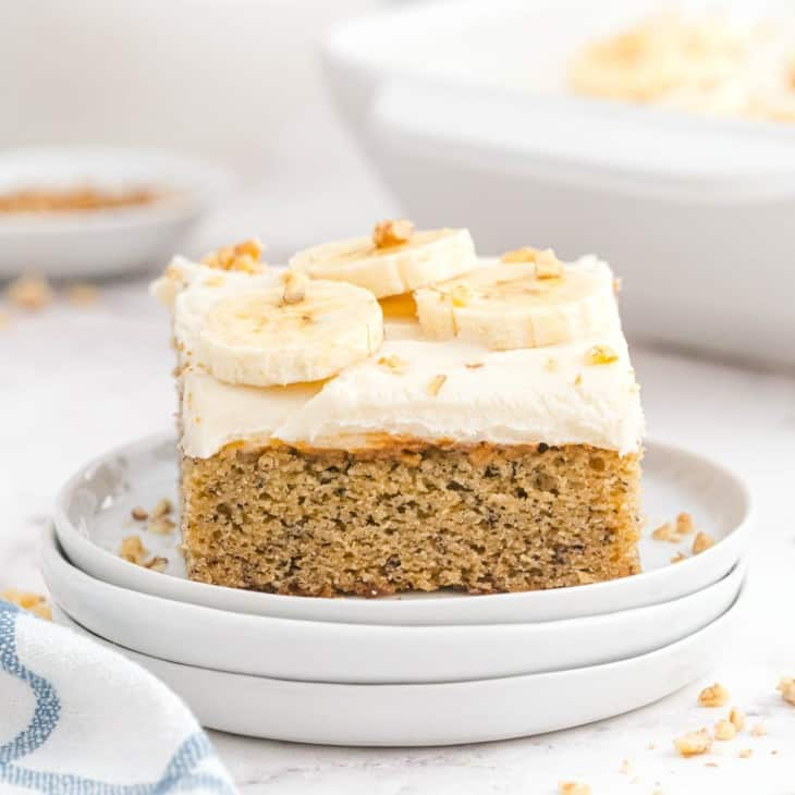 Banana cake with white cream cheese frosting, topped with bananas and nuts.