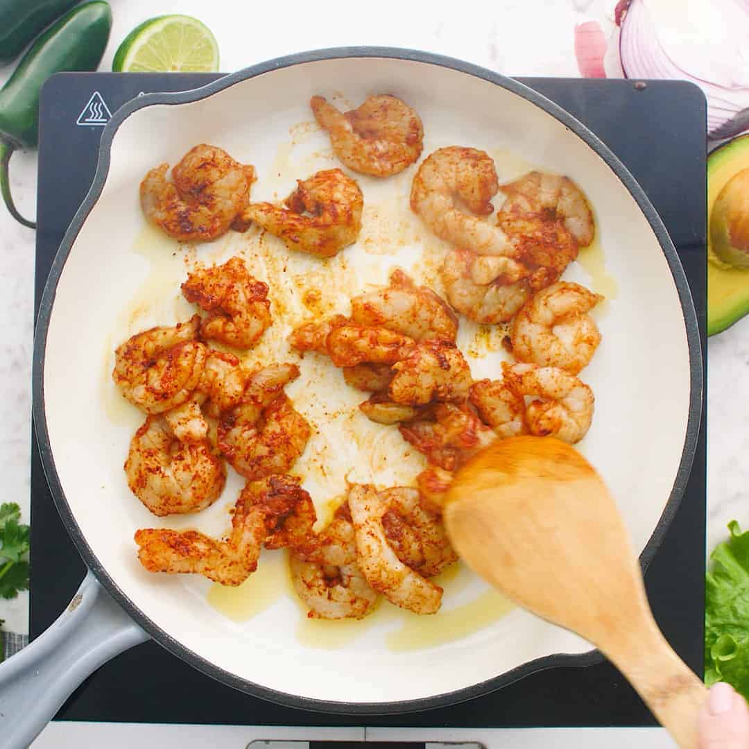 Shrimp cooking in a white skillet.