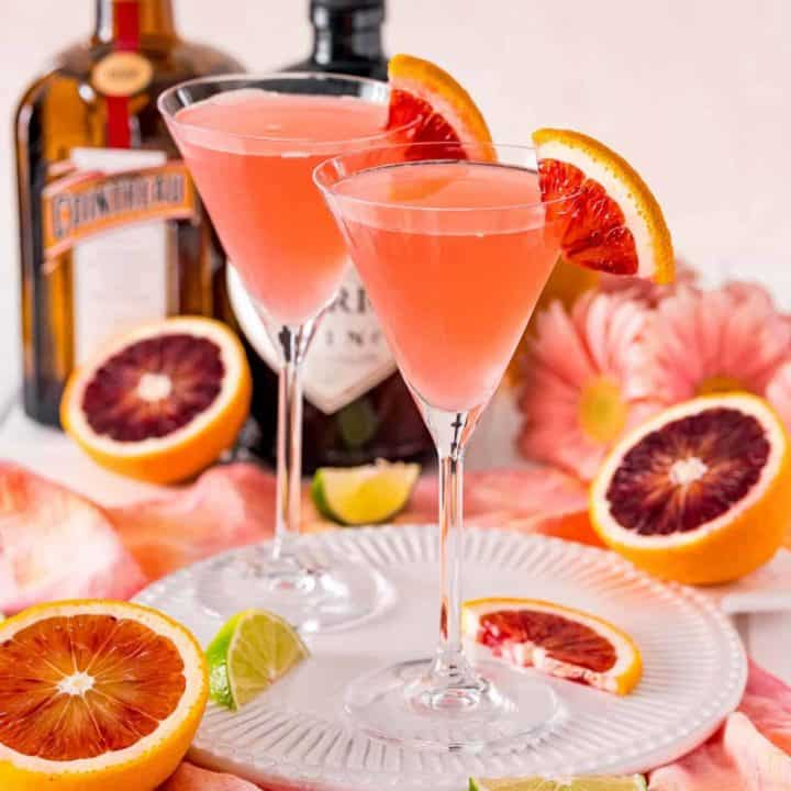 Two light pinkish red cocktails garnished with blood oranges, on a tray.