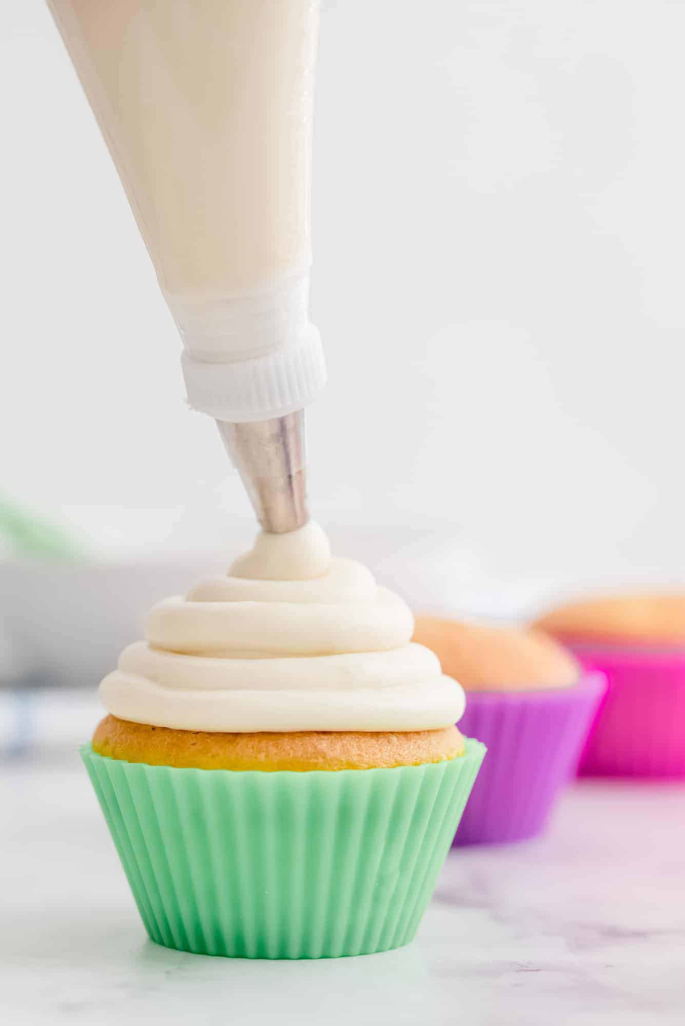 Cream cheese frosting being piped onto a cupcake with a colorful green liner.