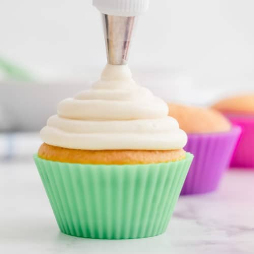Frosting being piped on a cupcake in a green liner.