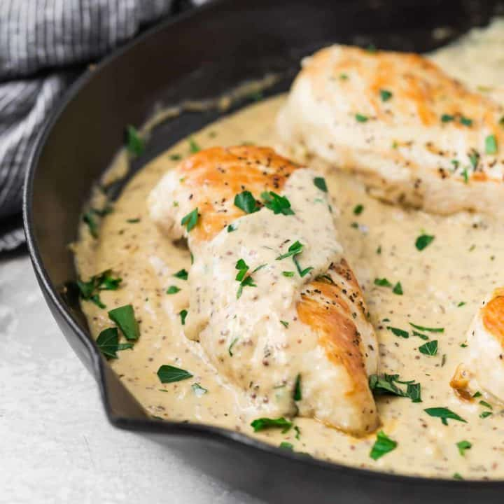 Chicken breast in a black pan with creamy mustard sauce.