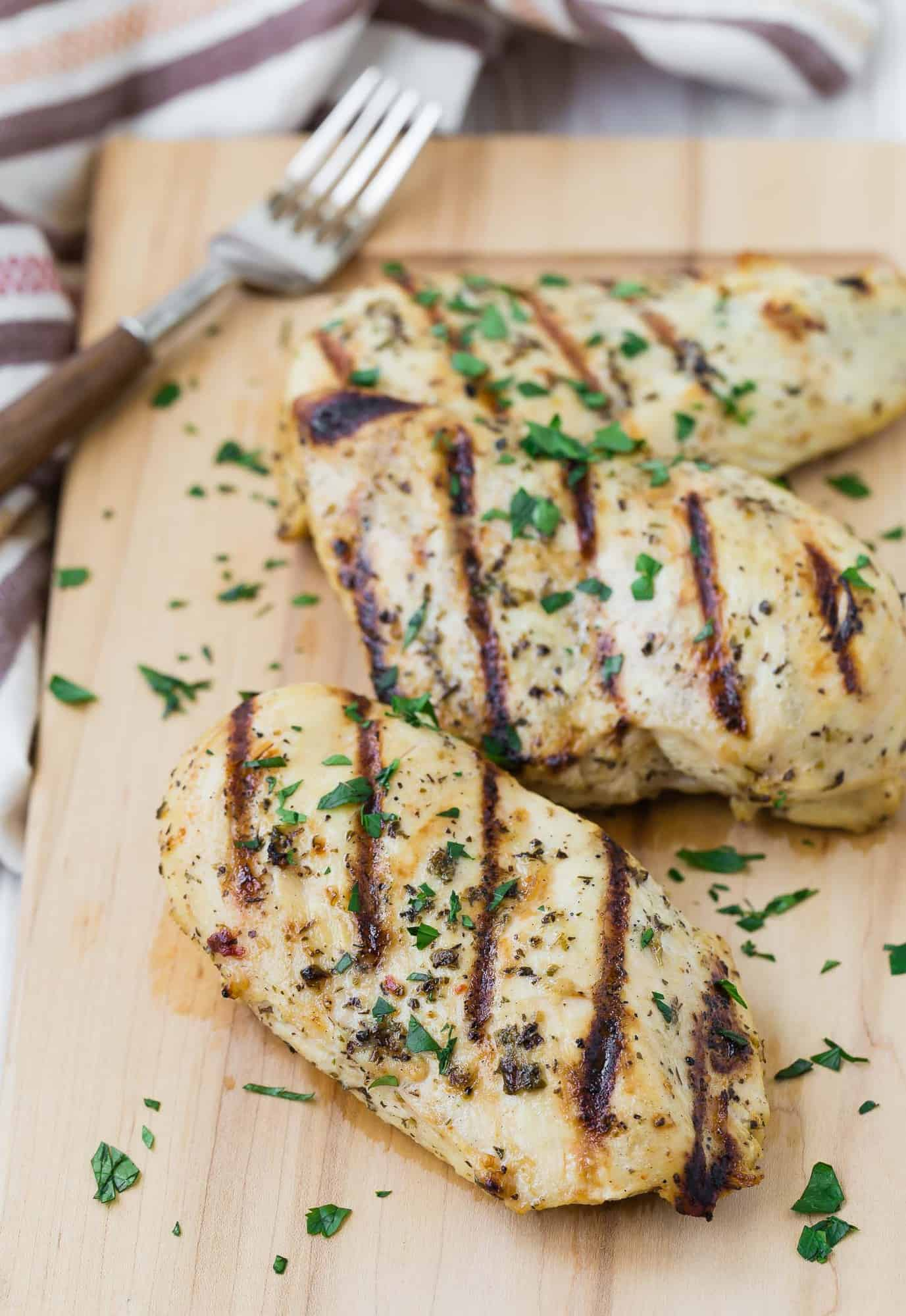 Three grilled boneless skinless chicken breasts on a wooden cutting board with a fork in the background.