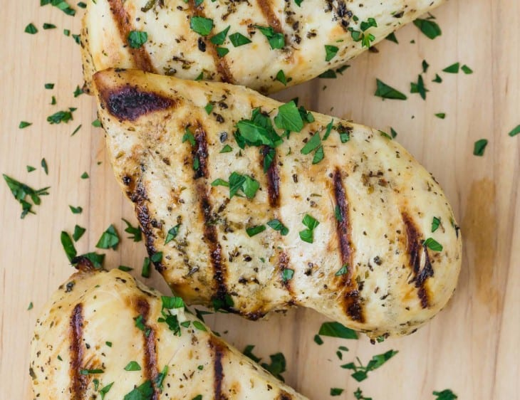 Close up view of a grilled chicken breast marinated in Italian chicken marinade. It is sprinkled with chopped fresh parsley.