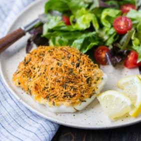 Parmesan baked cod on a plate with lemon wedges, a green salad, and a fork.