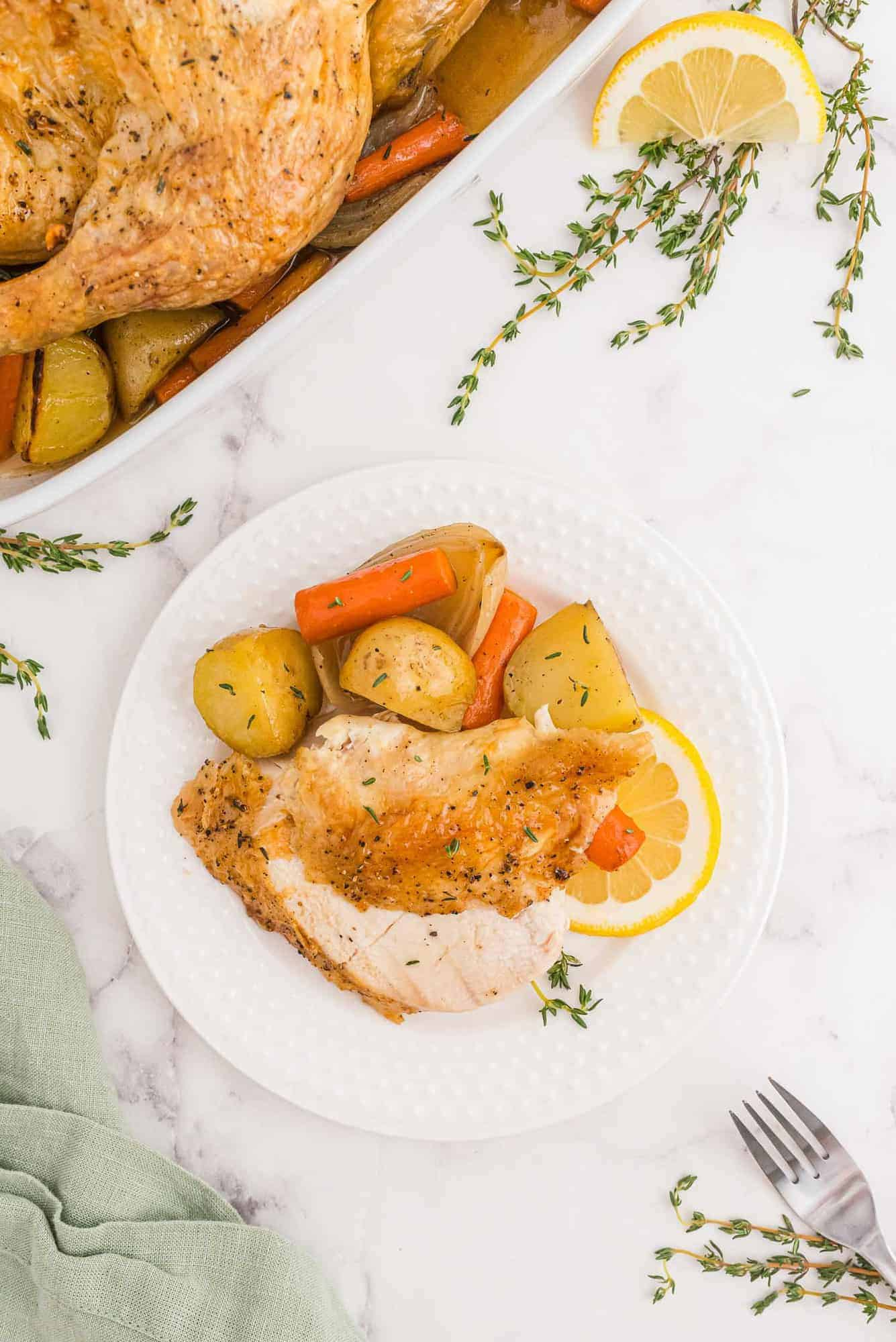 Carved chicken on a plate with vegetables and potatoes.