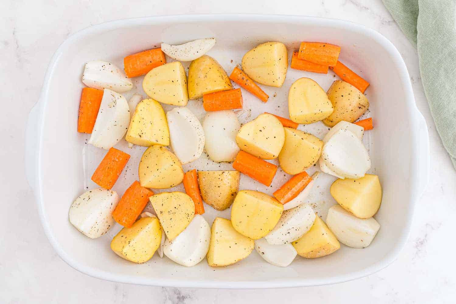 Potatoes, onions, and carrots in a white baking dish.