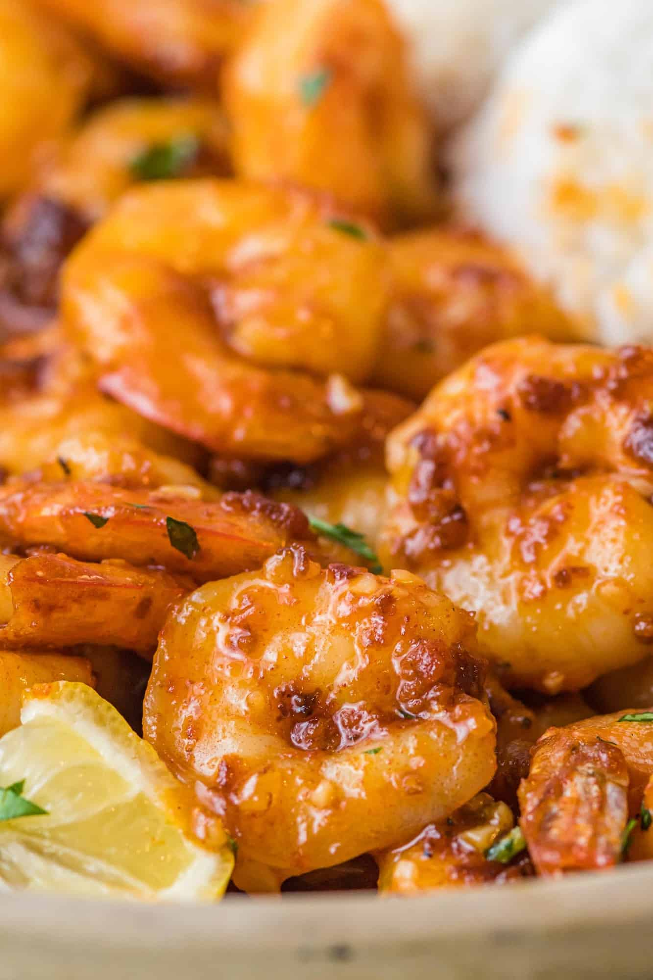 Close up of spicy honey garlic shrimp with lemon wedges and rice.