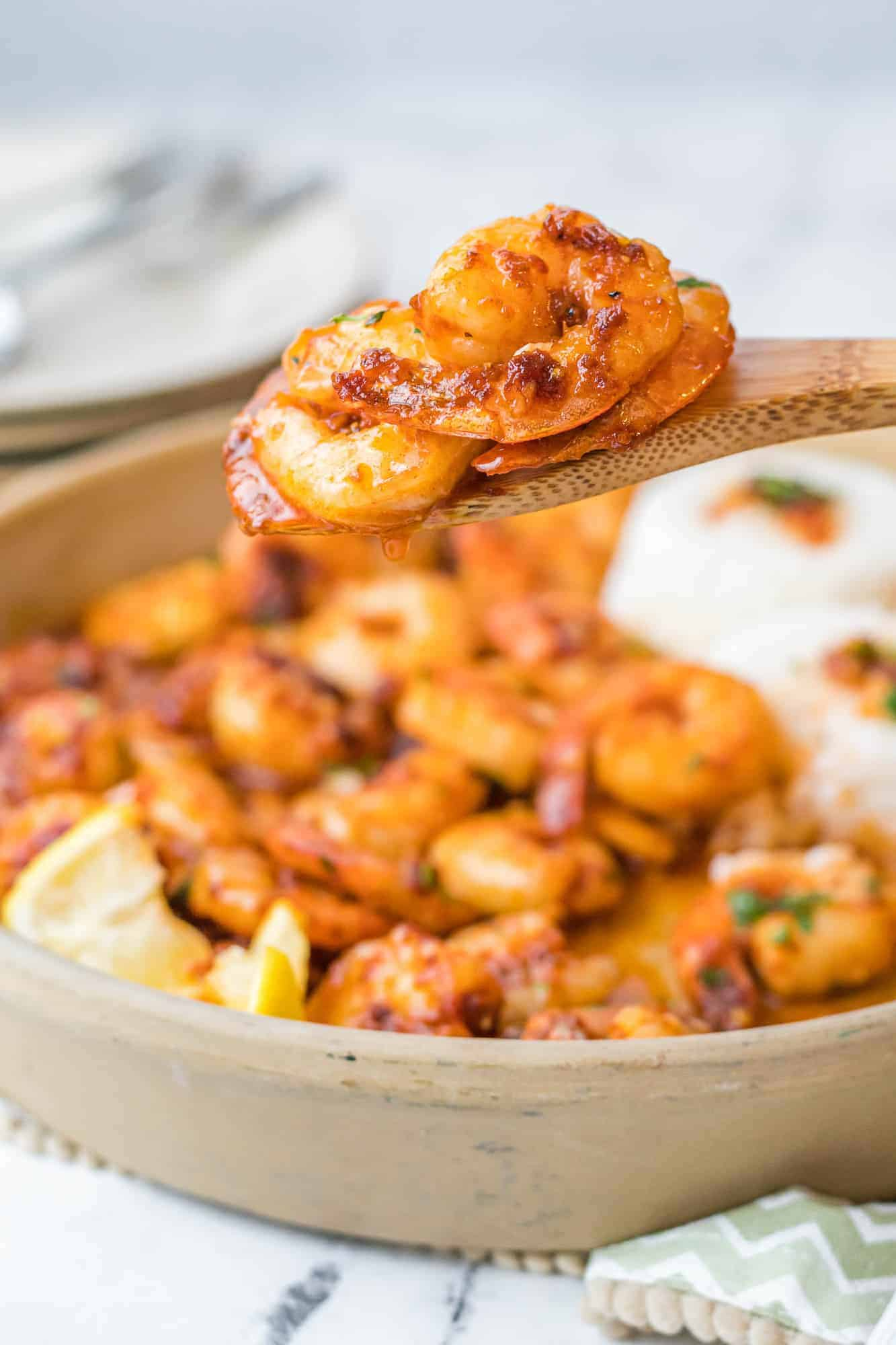 Seasoned and cooked shrimp on a serving spoon, more in the background.