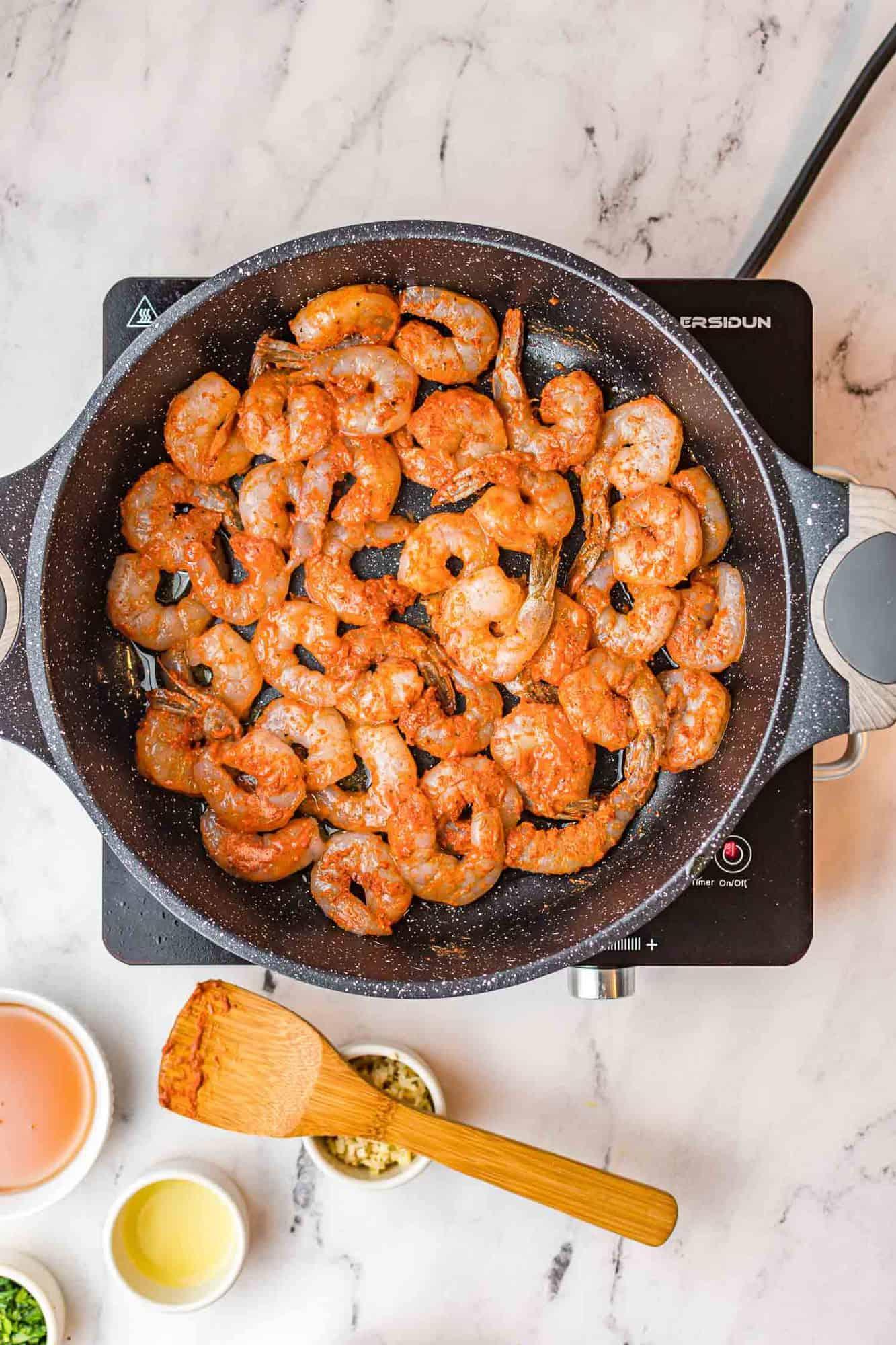 Seasoned shrimp in a skillet.