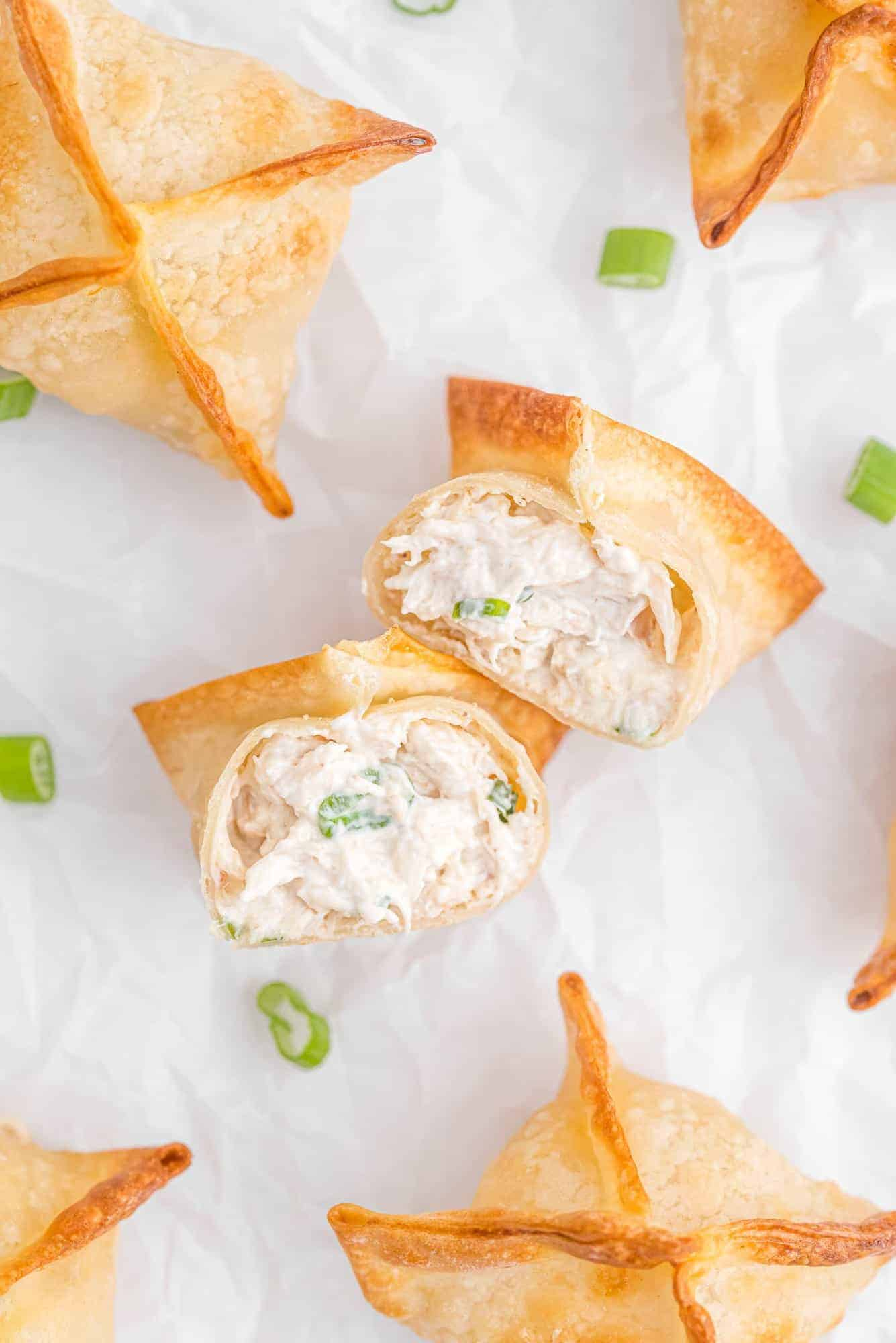 Overhead view of crab wontons with green onions.