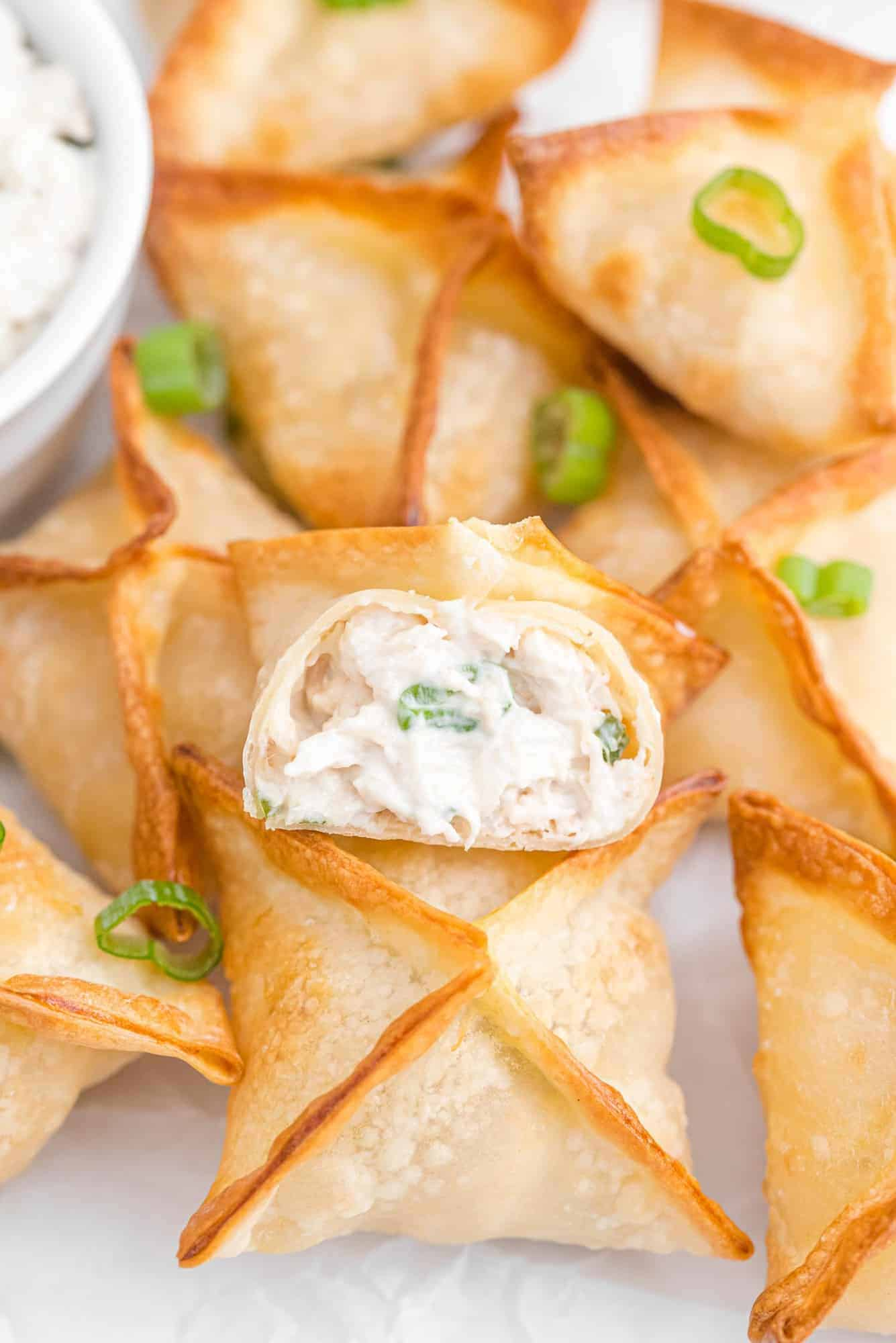 Crab rangoon on a plate with green onions