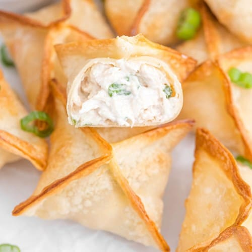 Air fryer crab rangoons, one split open to show filling.