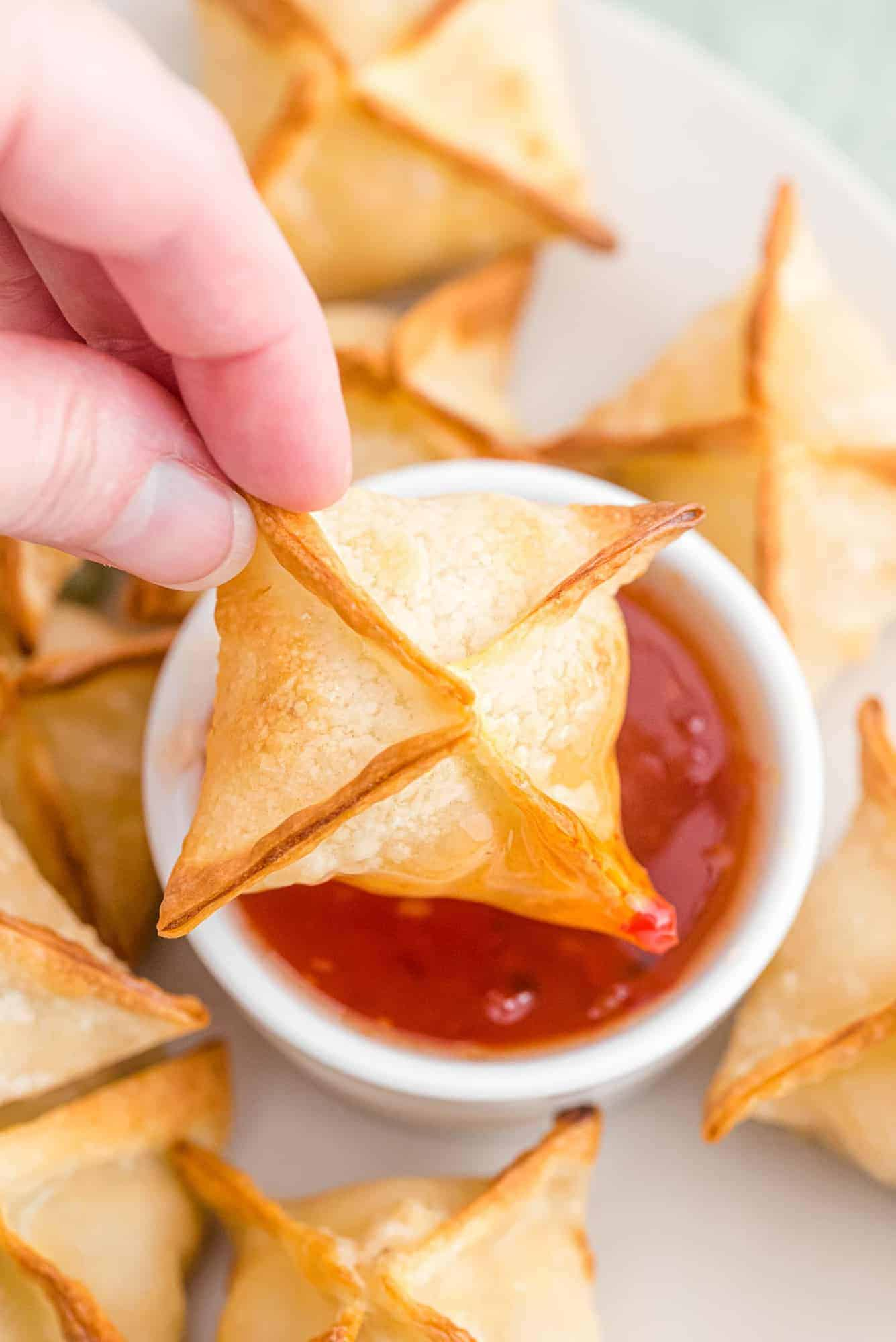 Crab wonton being dipped into a small bowl of sweet chili sauce.
