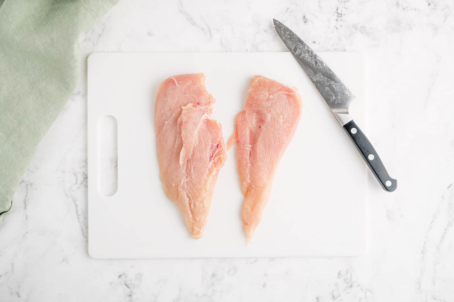 A chicken breast, cut in half to make thin cutlets.