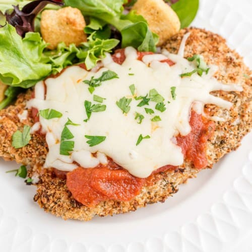Chicken parmesan on a white plate with a green salad.