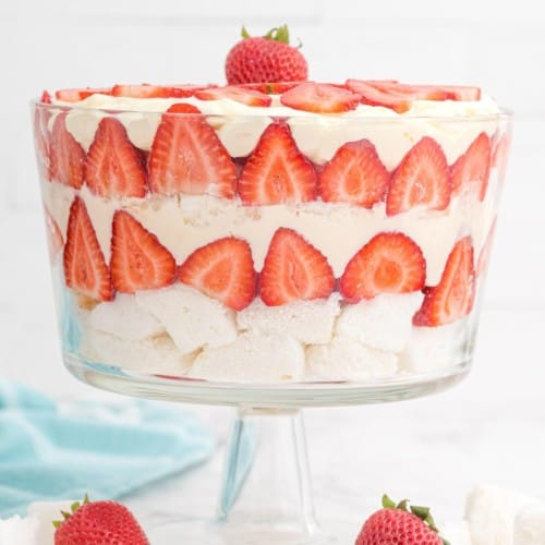 Layered strawberry trifle in a clear glass trifle bowl.