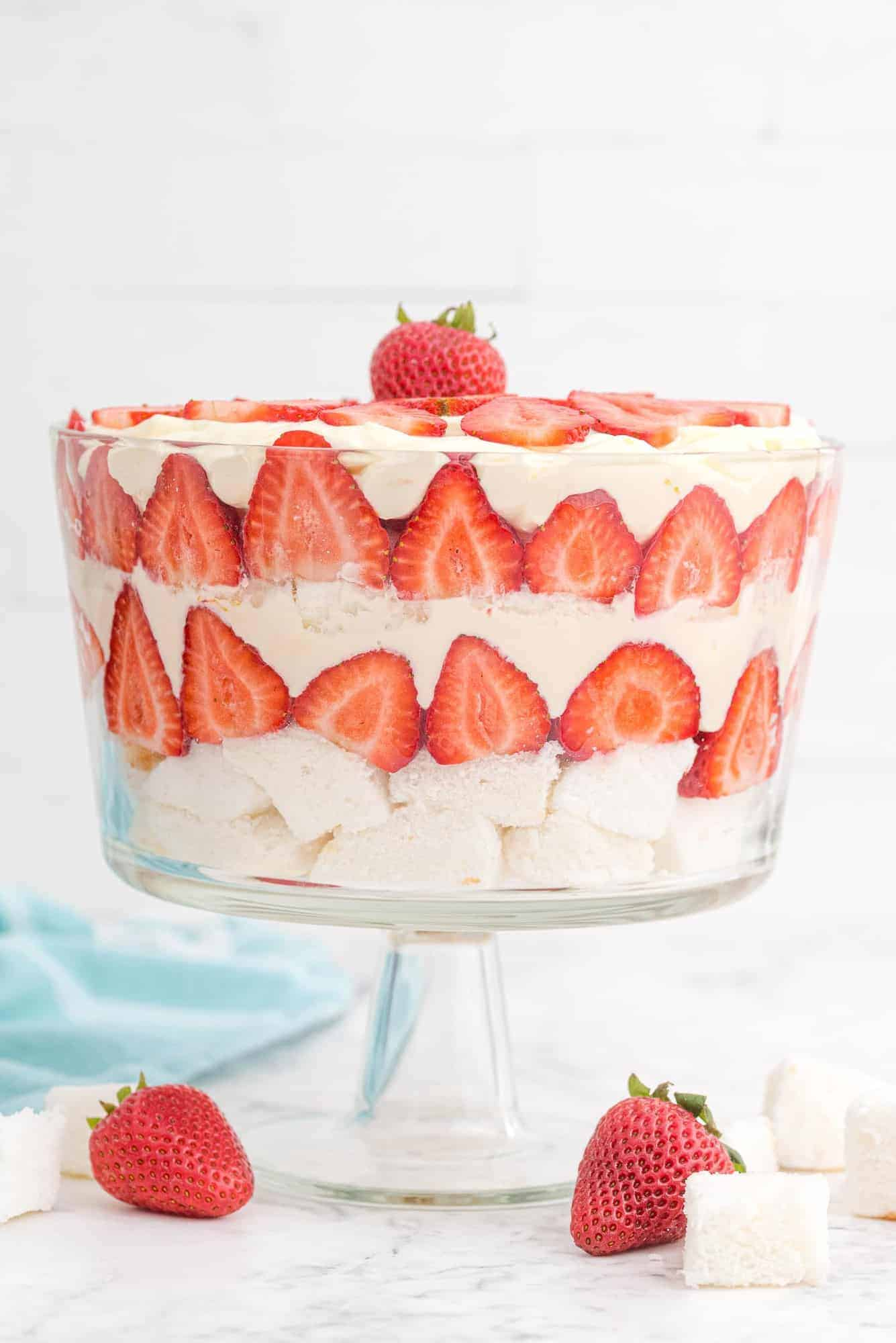 Strawberry trifle in clear glass trifle bowl against white background.