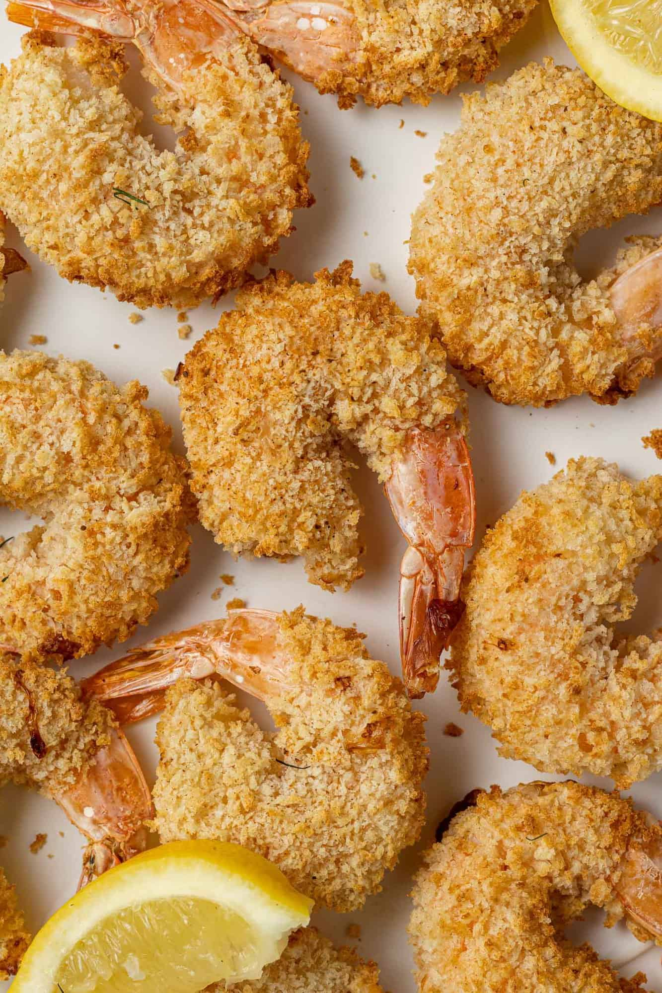 Perfectly breaded shrimp laid out in a single layer with a couple lemon slices.
