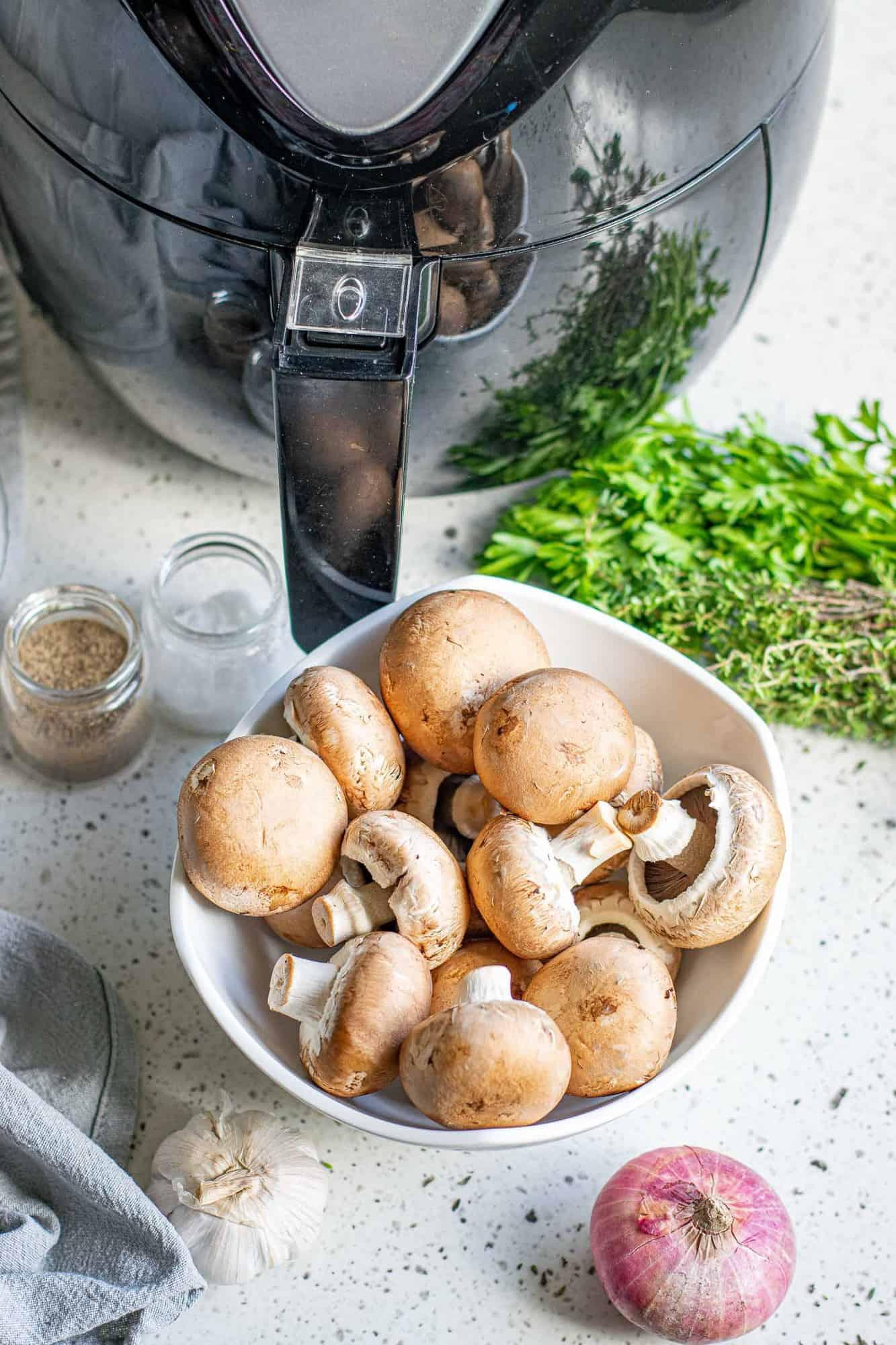 Air fryer, a bowl of fresh mushrooms, a shallot, and fresh herbs.