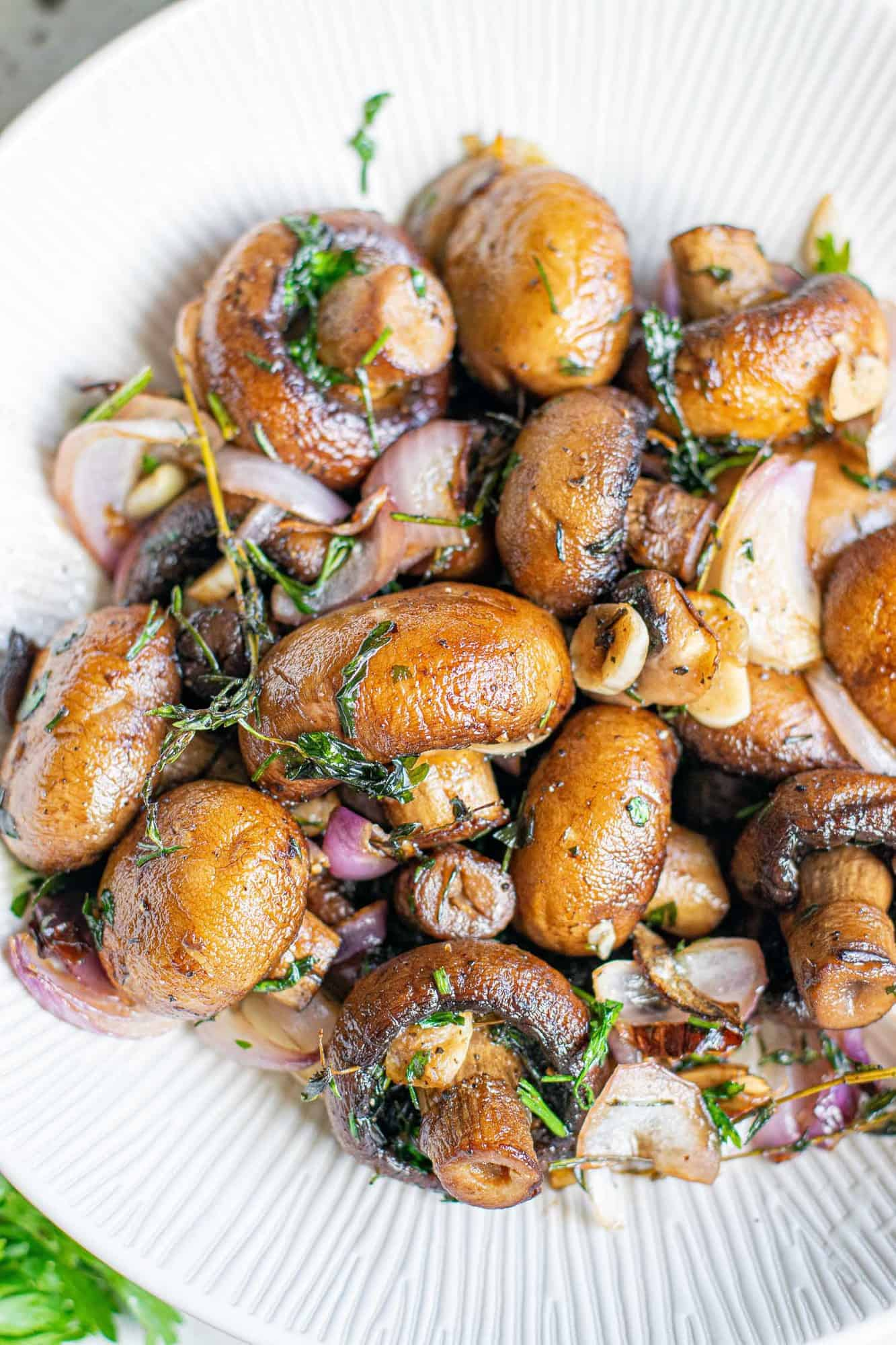 Golden brown cooked mushrooms in a white bowl.