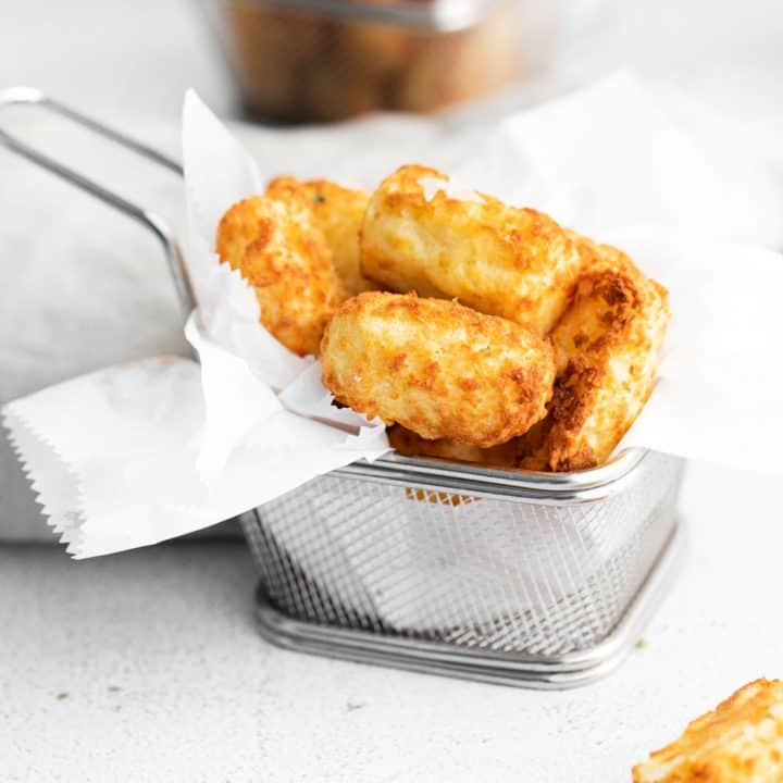 Air fryer tater tots in a tiny metal basket.