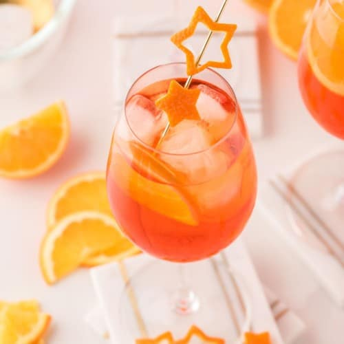 An light orange aperol spritz in a wine glass garnished with orange peel cut into the shape of a star.