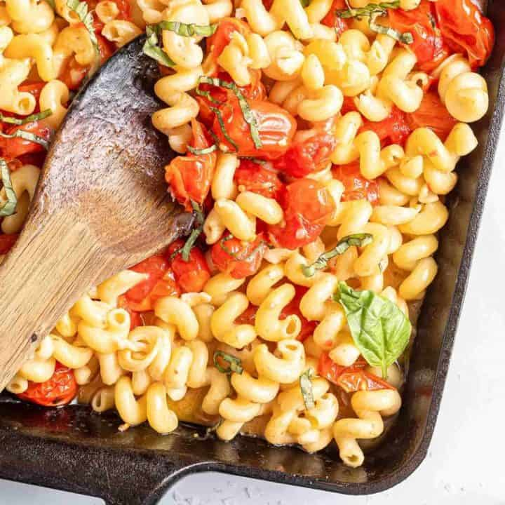 Pasta with feta and tomatoes, in a black baking dish with wooden spoon.