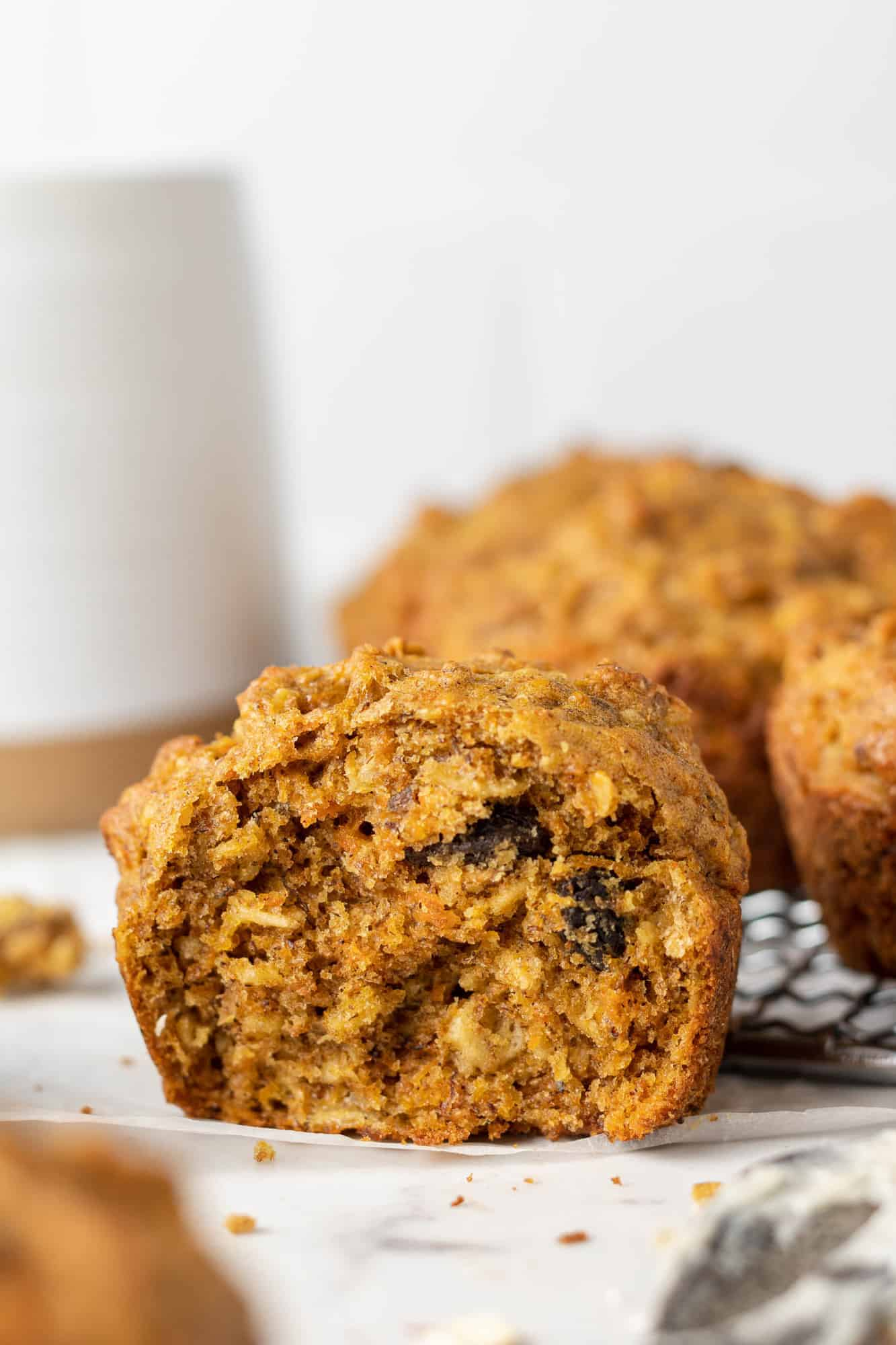 Muffin torn in half to show interior: carrots, oats, and raisins are visible.