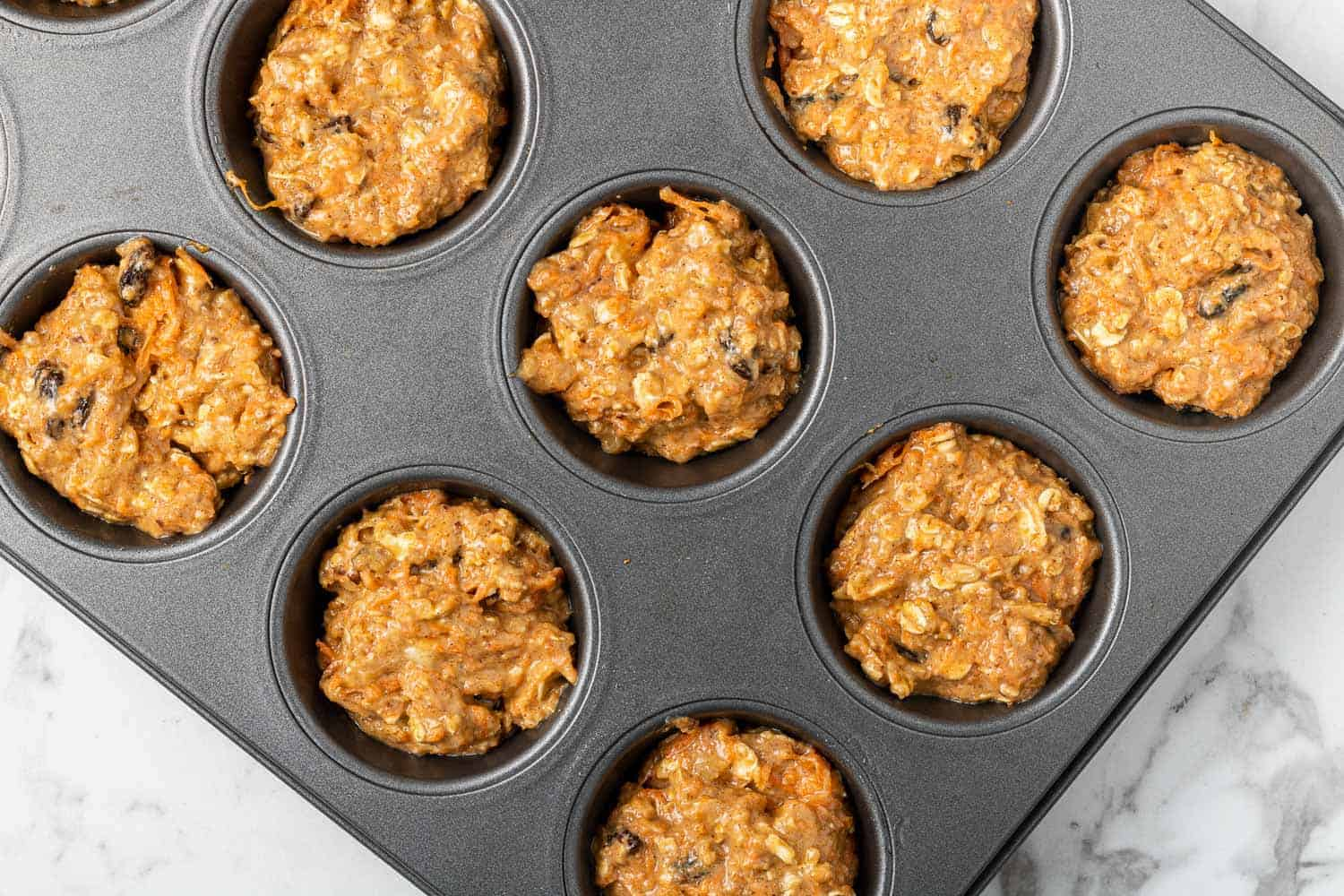 Unbaked muffins in a muffin tin.