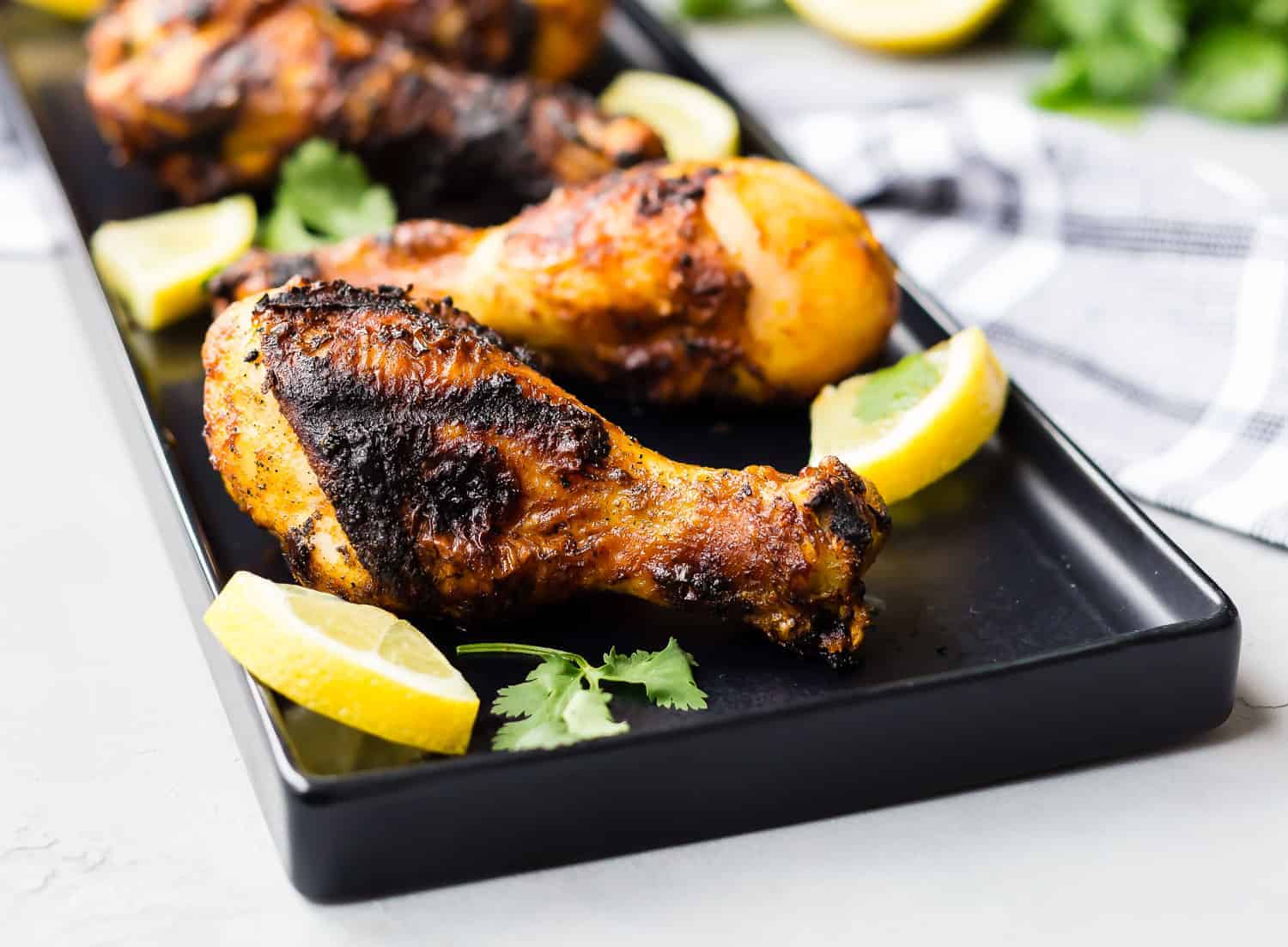 Grilled chicken drumsticks on a black platter with lemon slices and cilantro.