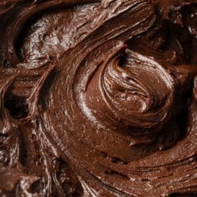 Close up of chocolate buttercream frosting, swirled to show texture.