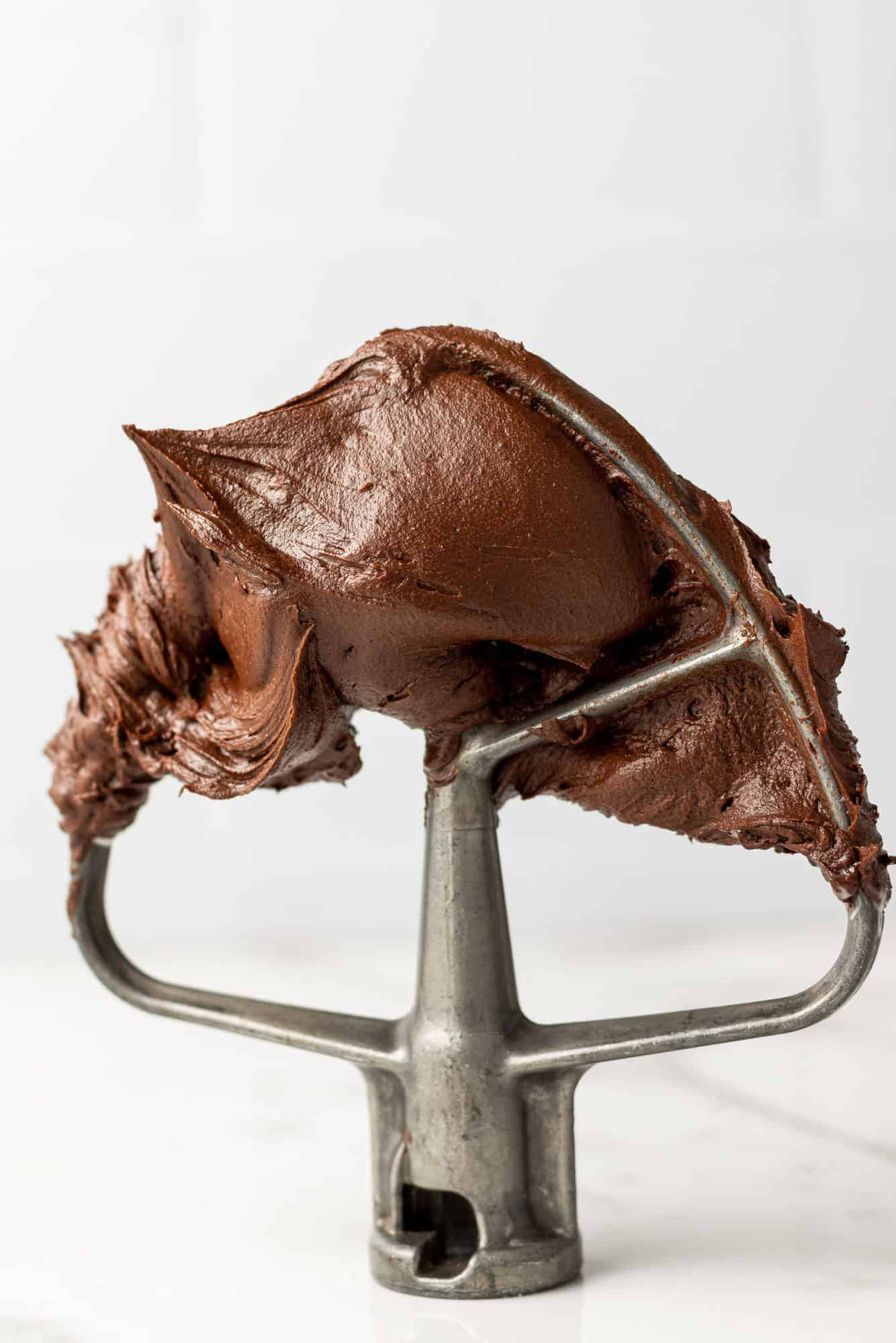 Chocolate buttercream frosting on a mixer beater.