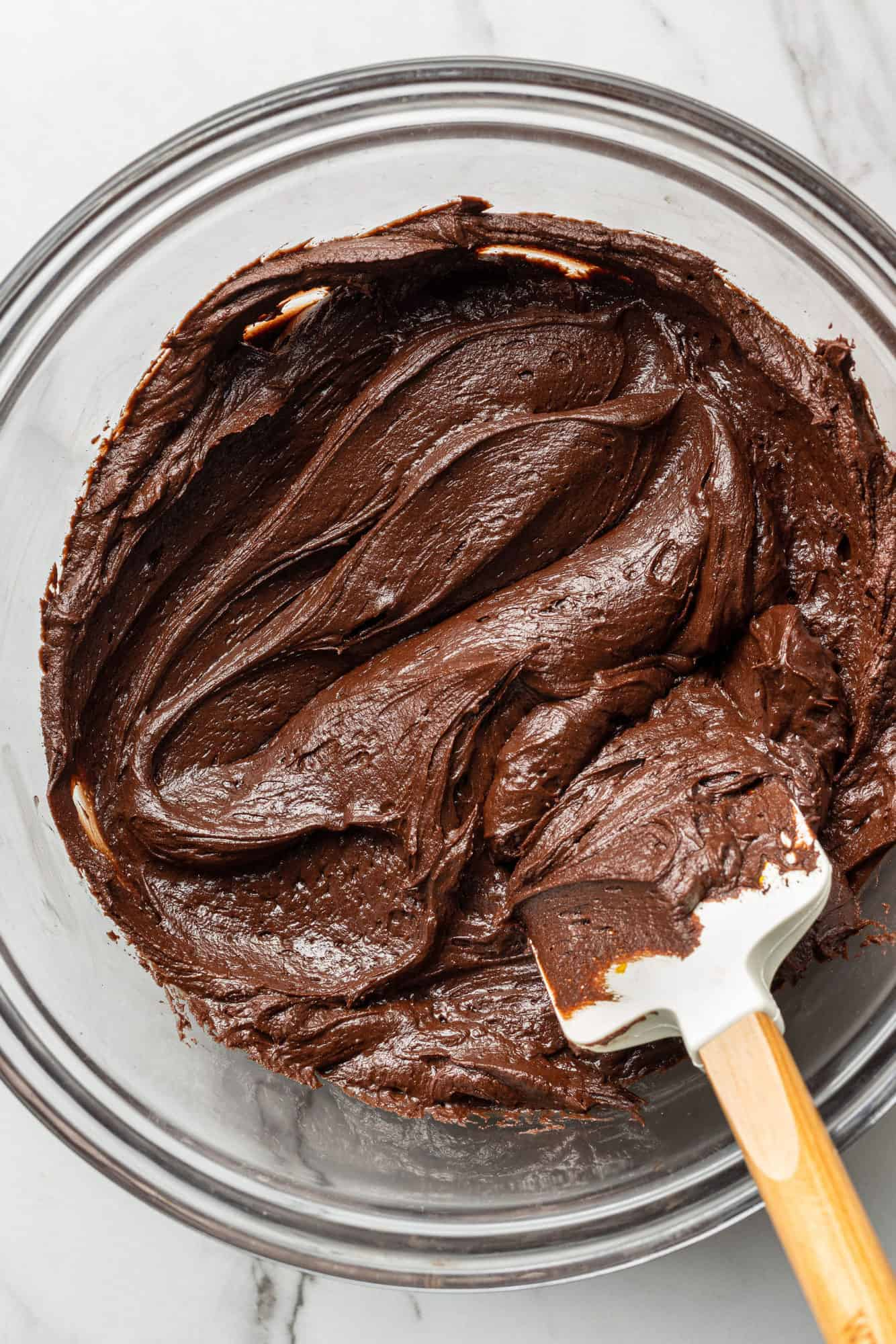 Chocolate frosting in a bowl with a spatula.